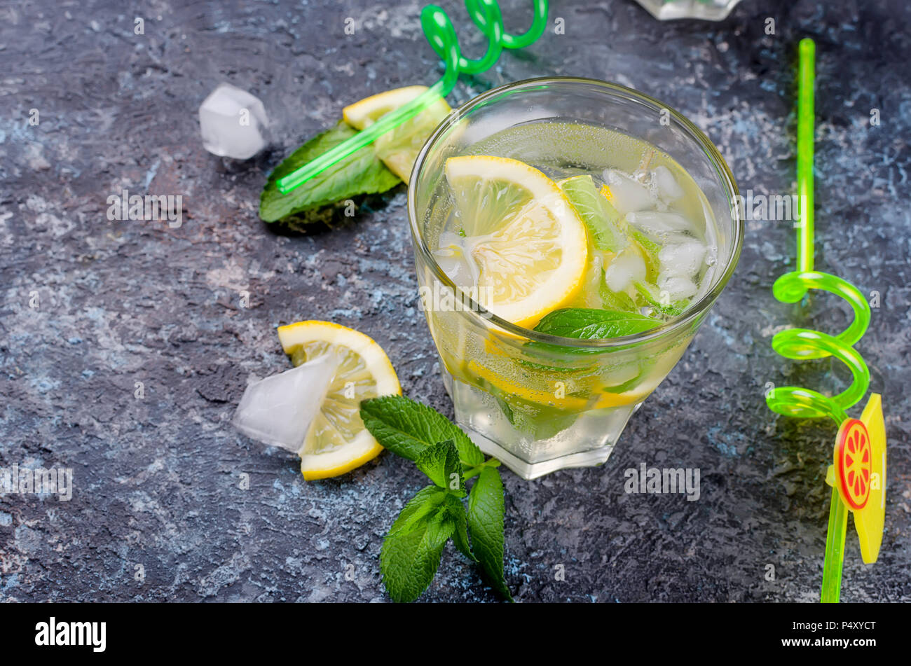 Fresh cold Mojito Cocktail with soda, ice, mint and lemon in glass and ingredients on a dark background, copy spase, selective focus - Stock Image