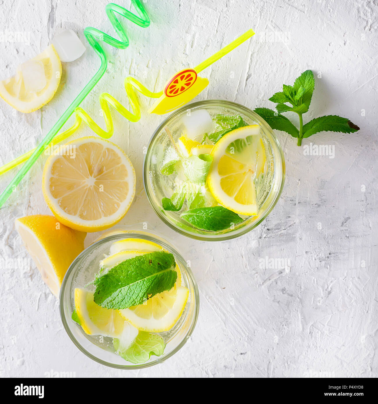 Fresh cold Mojito Cocktail with soda and lemon in glass and ingredients on a light background - Stock Image