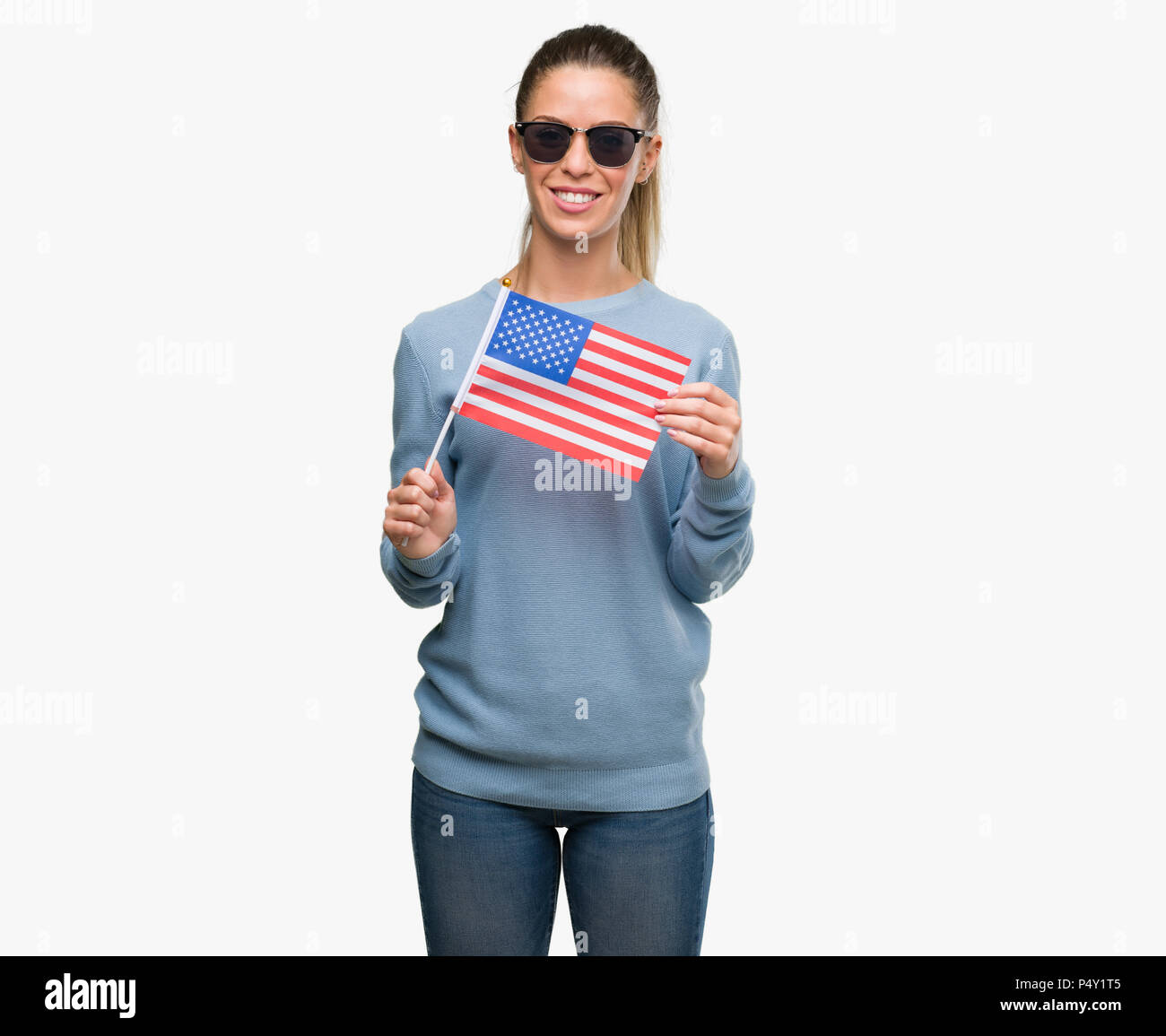 Beautiful young woman holding USA flag with a happy face standing and smiling with a confident smile showing teeth - Stock Image