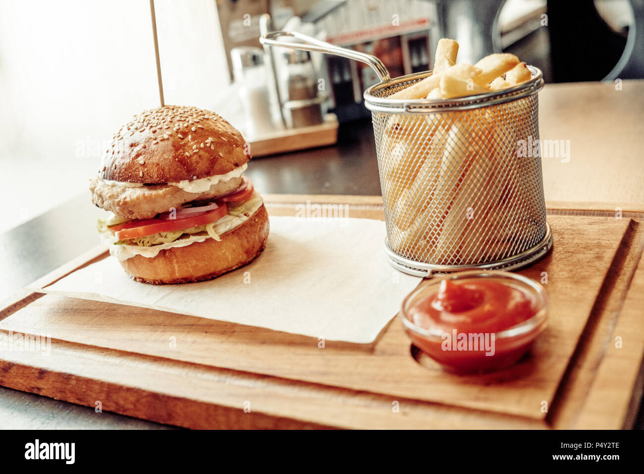 Angle View Of Craft burger , tomato souse and french fries on wooden plate - Stock Image