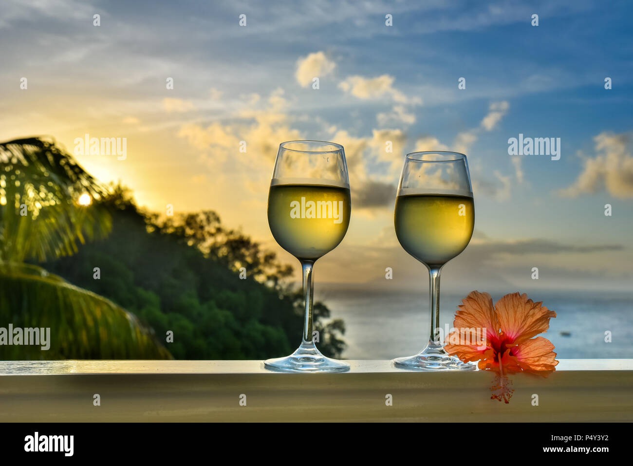 Romantic moments in summer at sunset with two glasses of white wine - Relaxing romantic holiday concept with beautiful view of tropical beach and coas Stock Photo