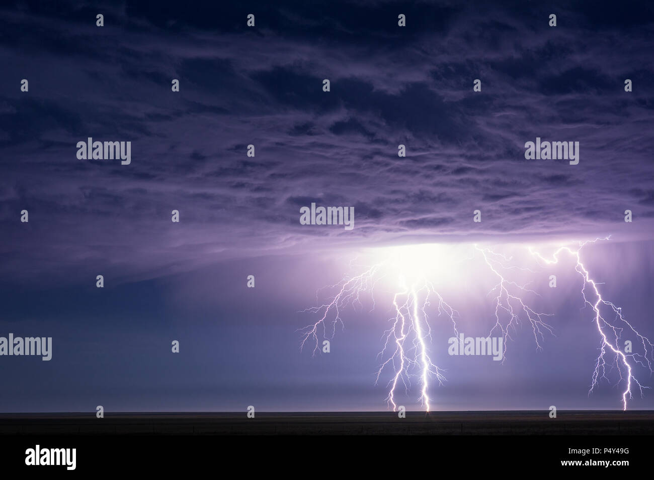 Lightning strikes and illuminates dramatic storm clouds during a summer thunderstorm near Eads, Colorado, - Stock Image