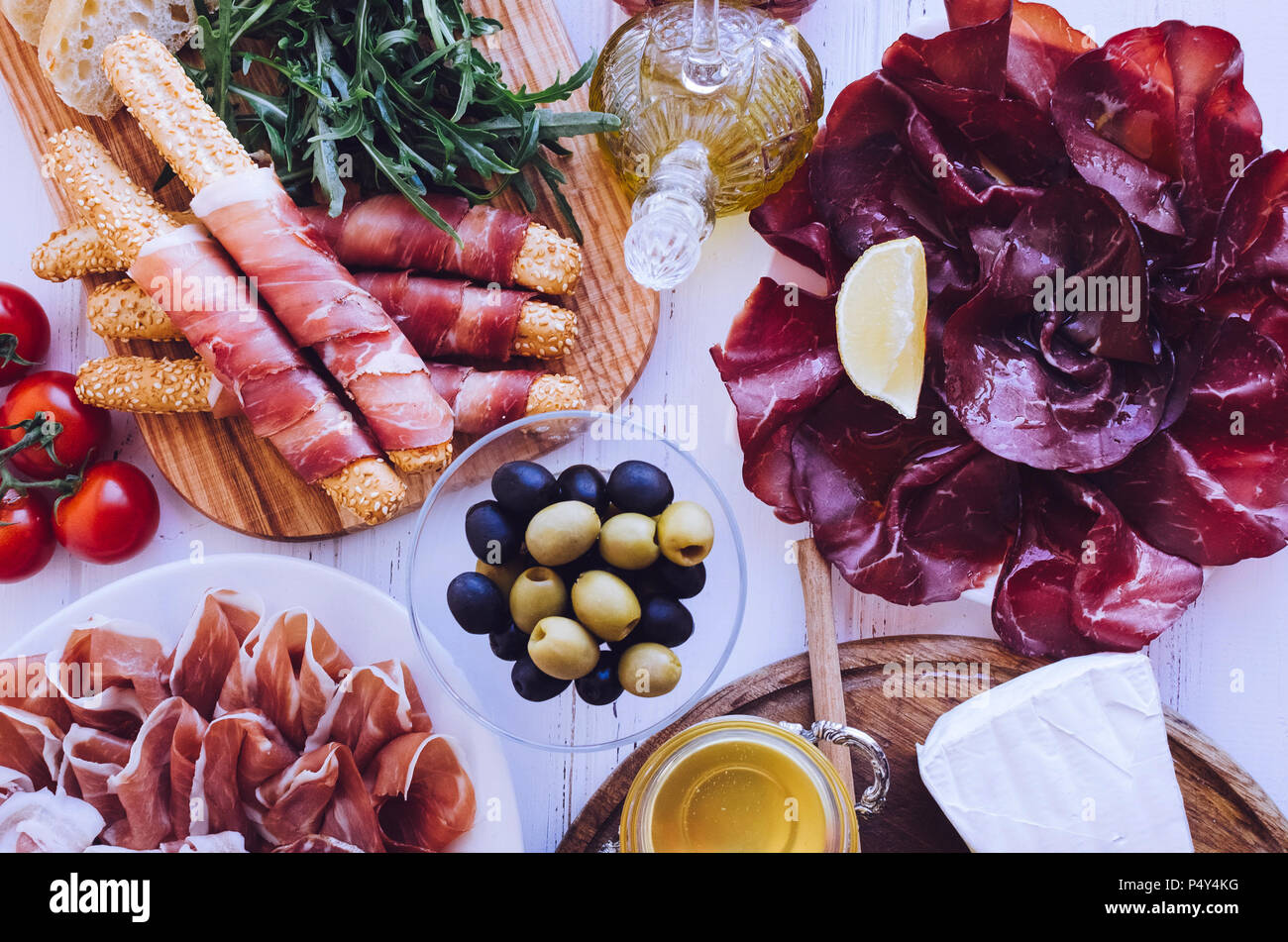 Table full of mediterranean appetizers, tapas or antipasto. Assorted Italian food set. Delicious snack on party or picnic time. Chopping board with me - Stock Image