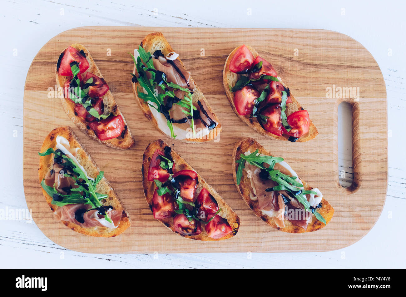 Selection of tasty Italian bruschetta or canapes on toasted baguette topped with tomatoes, Prosciutto di Parma, arugula and balsamic glasse sauce on c - Stock Image