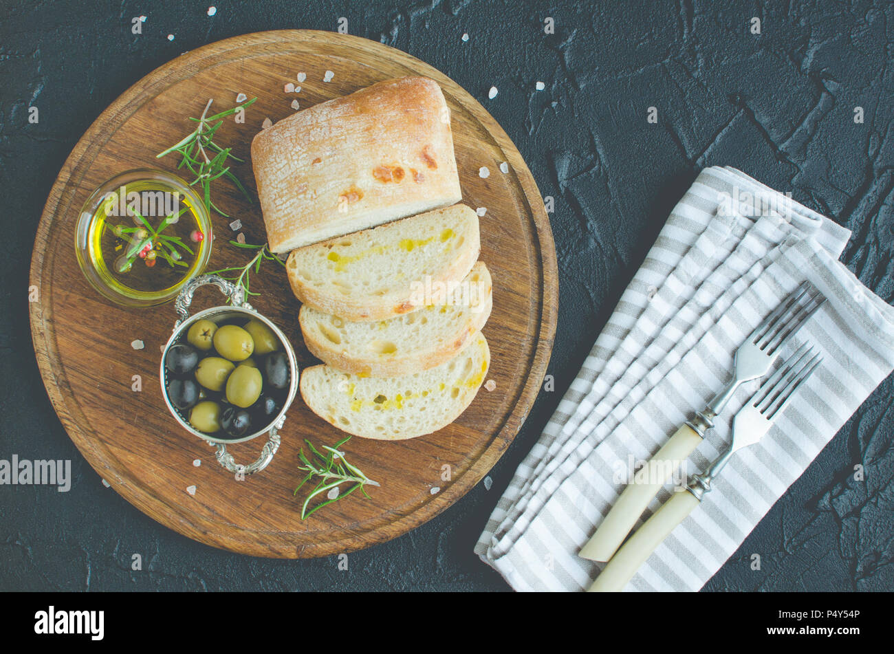 Mediterranean snacks set. Green and black olives, olive oil, herbs and sliced ciabatta bread on wooden board over dark stone background. Italian food  - Stock Image