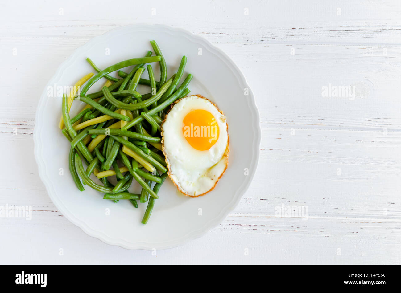 Cooked green beans with fried egg in white plate on wooden background with space for text. Healthy vegetarian food concept. Top view. Copy space. - Stock Image