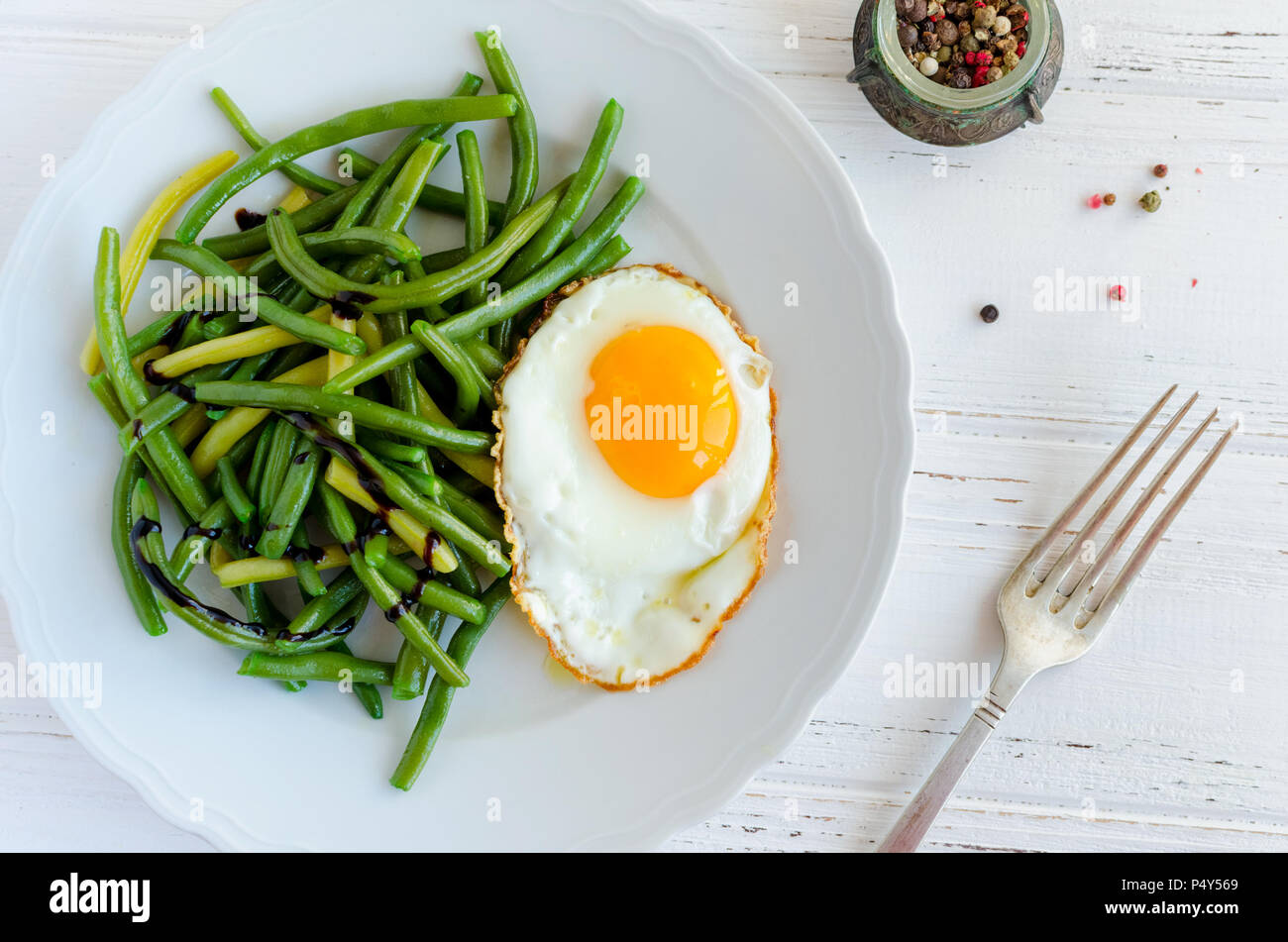 Cooked green beans with sauce balsamico glassa and fried egg in white plate on wooden background with fork. Healthy vegetarian food concept. Top view. - Stock Image