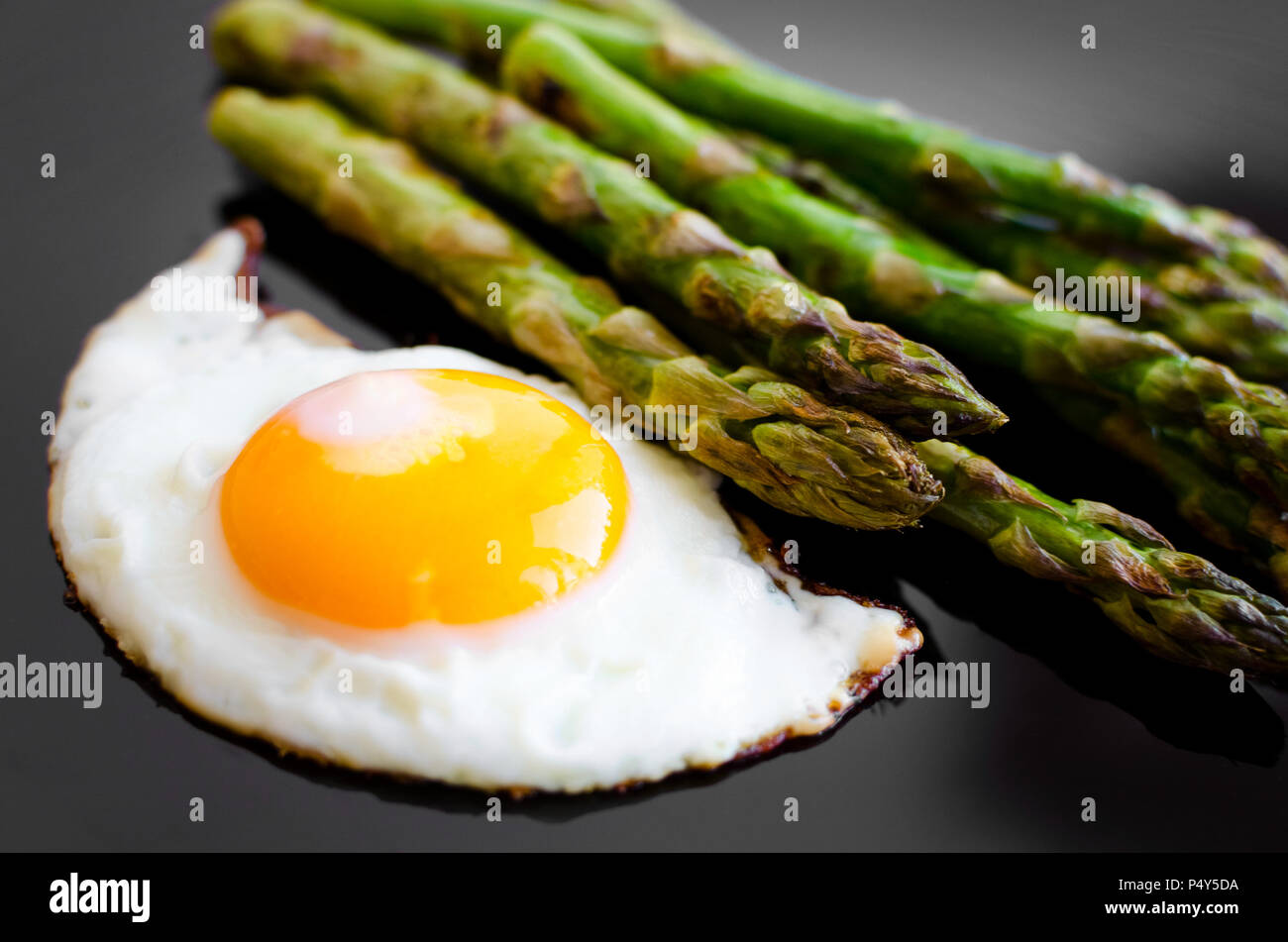 Fried egg and roasted fresh asparagus in black plate. Healthy lunch concept. Delicious, nutritious eating. - Stock Image