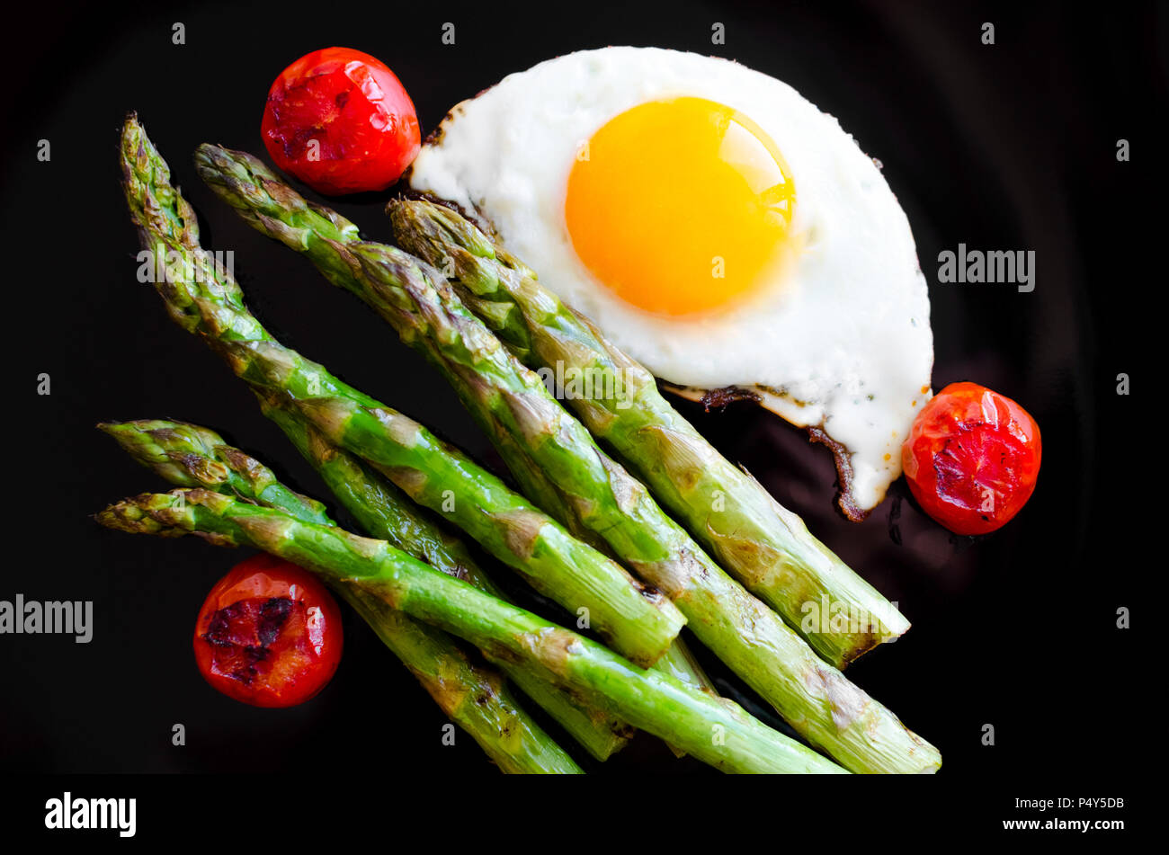 Fried egg and roasted fresh asparagus with tomatoes cherry in black plate. Healthy lunch concept. Delicious, nutritious eating. Top view. - Stock Image