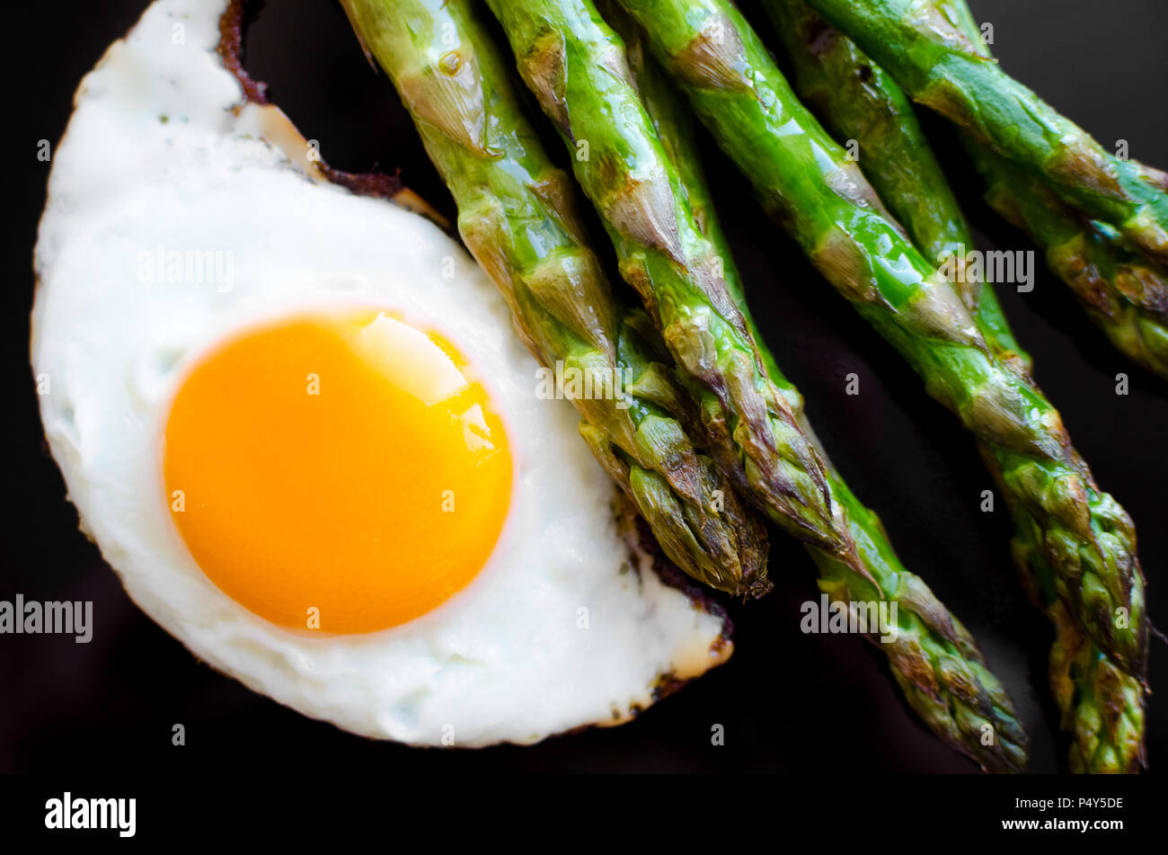 Fried egg and roasted fresh asparagus in black plate. Healthy lunch concept. Delicious, nutritious eating. Top view. - Stock Image