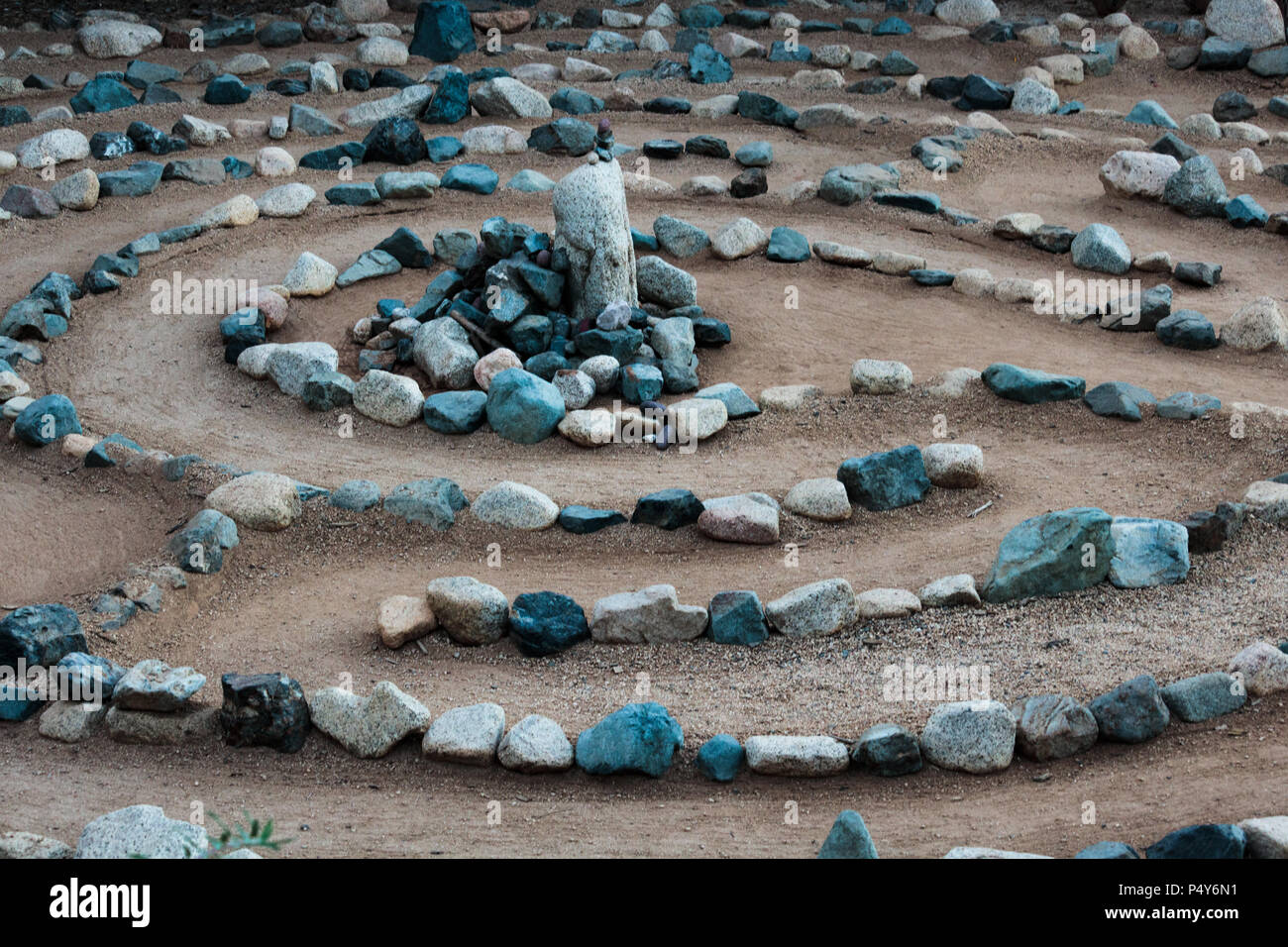 Traditional natural stone walking labyrinth mazze for contemplation and worship, created with rocks in shades of blue and turquoise. A calm, peaceful - Stock Image
