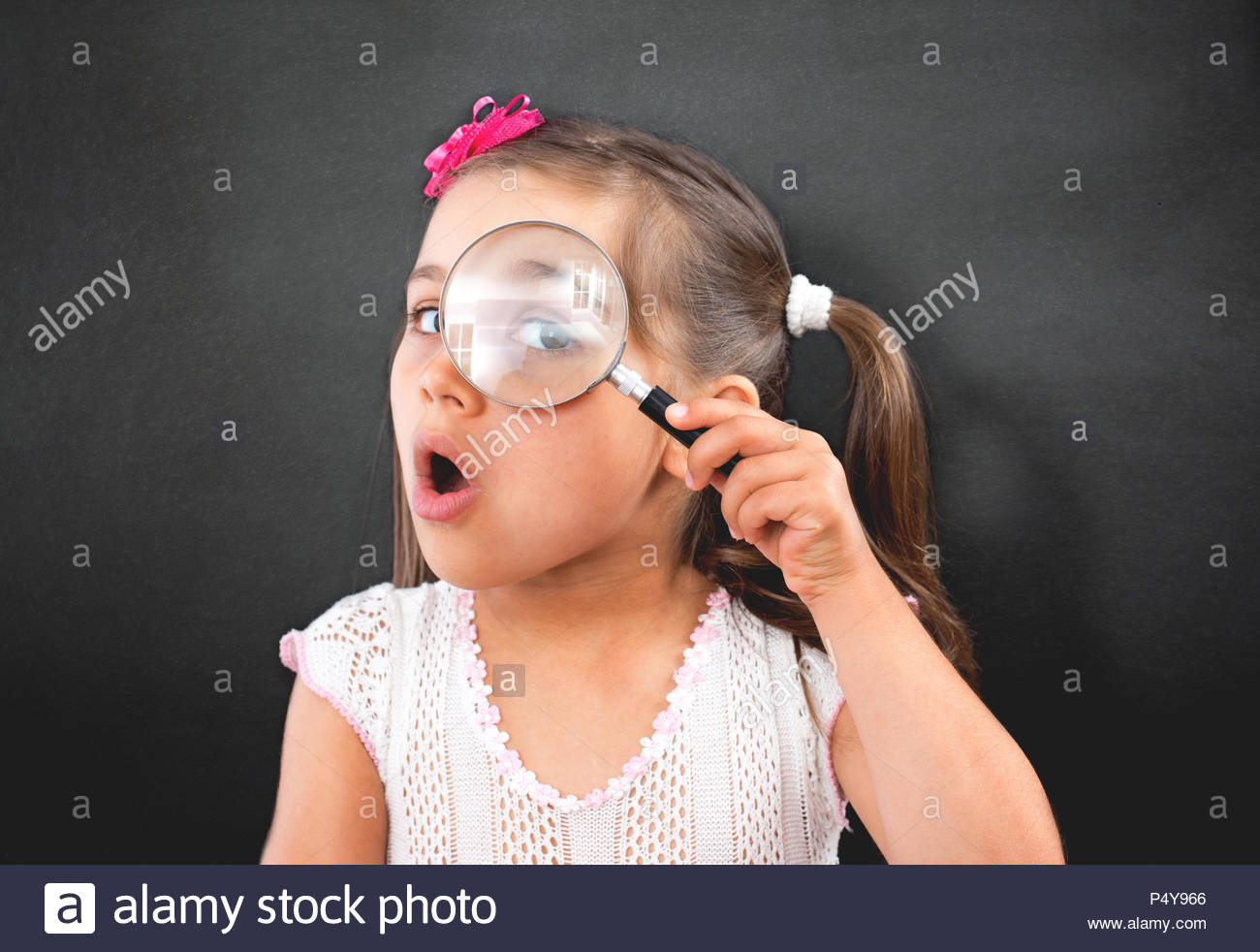 Portrait of Curious Little Child Girl Looking Through Magnifying Glass - Stock Image