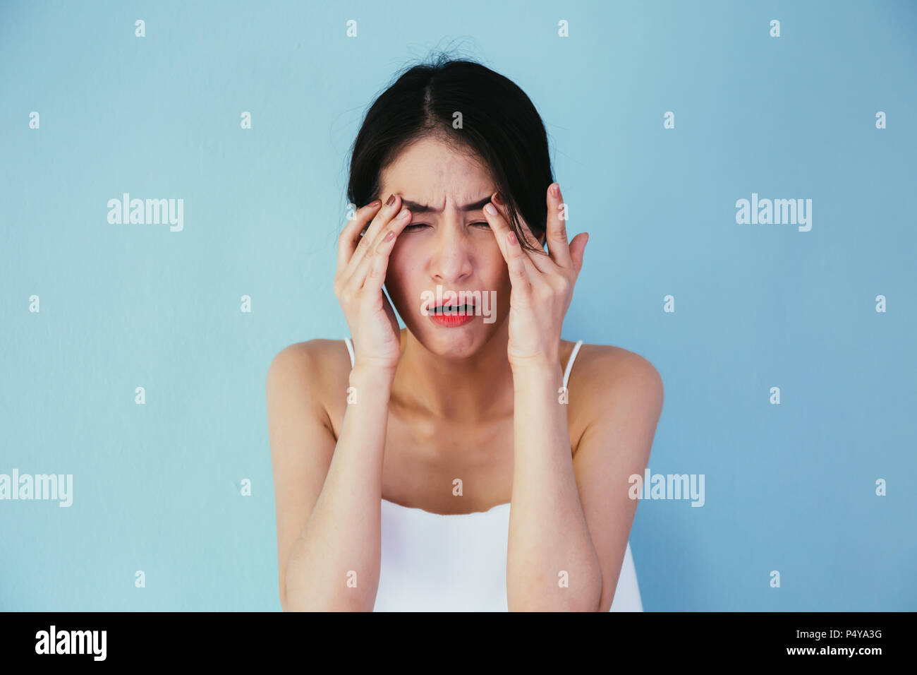 Young Asian woman having eye pain and soreness isolated over blue background - Healthcare and Medical concept - Stock Image