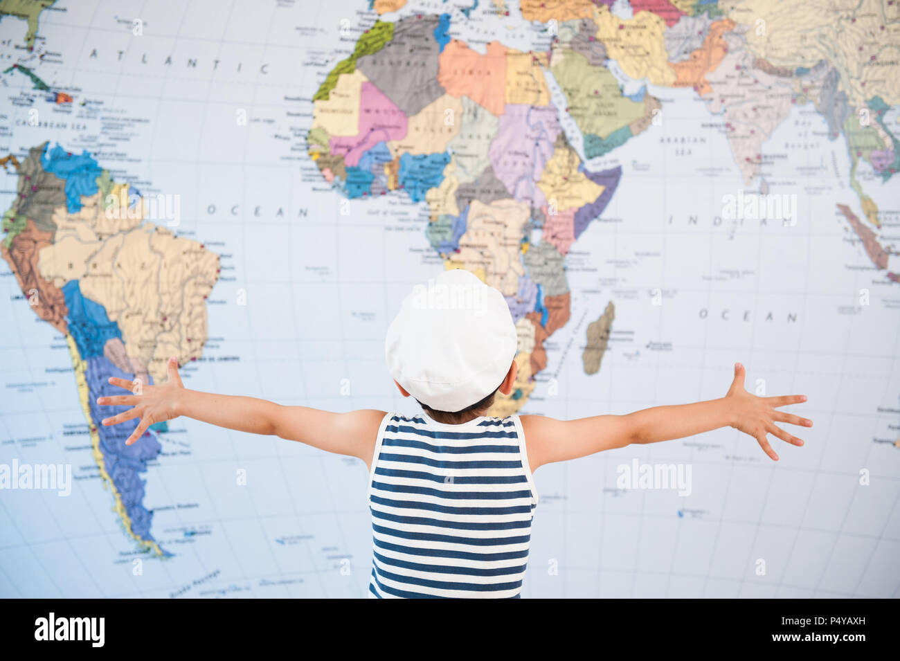 little child in captain hat spreading hands to world map Stock Photo