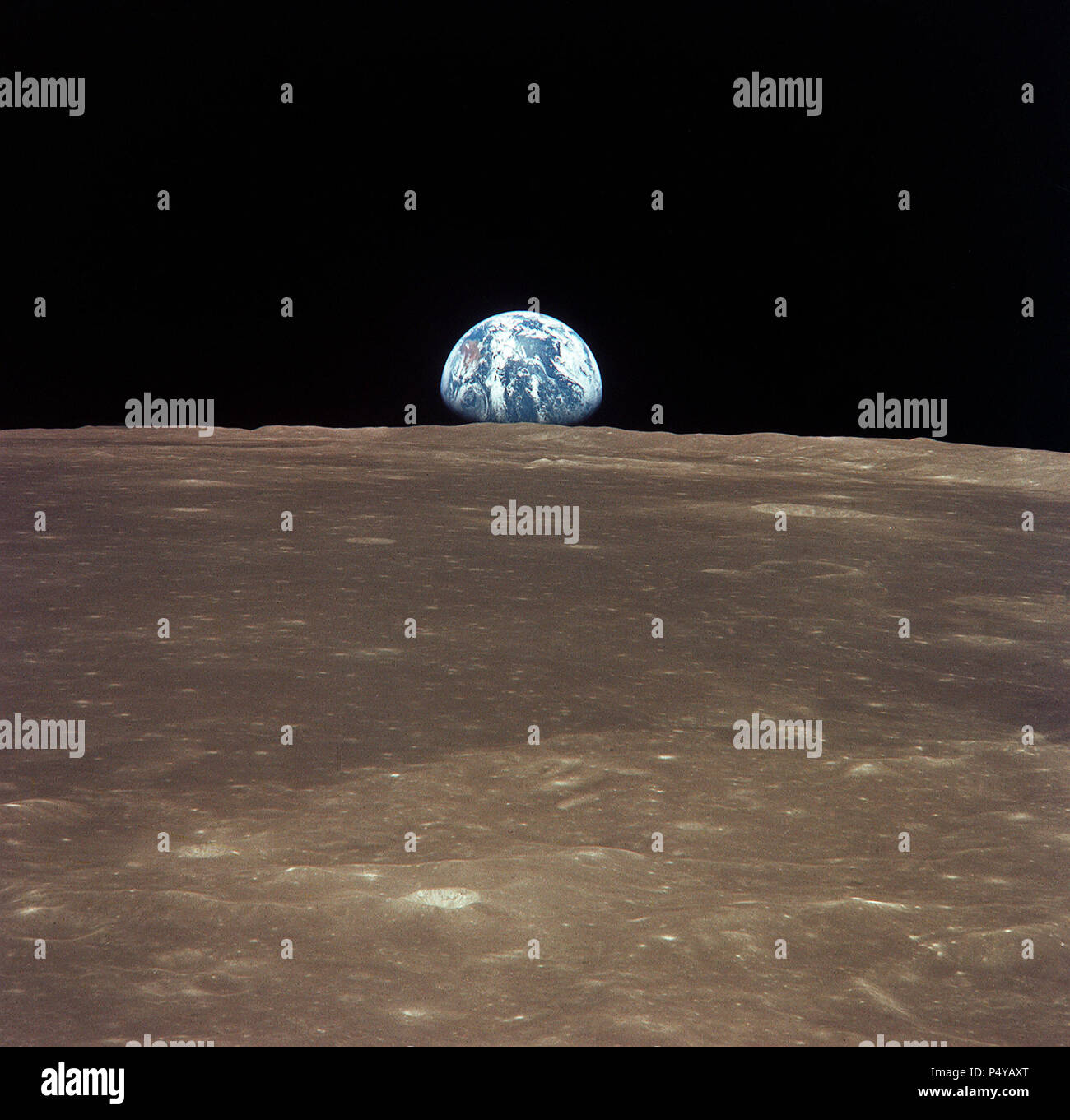 This view from the Apollo 11 spacecraft shows Earth rising above the moon's horizon. The lunar terrain pictured is in the area of Smyth's Sea on the nearside - Stock Image