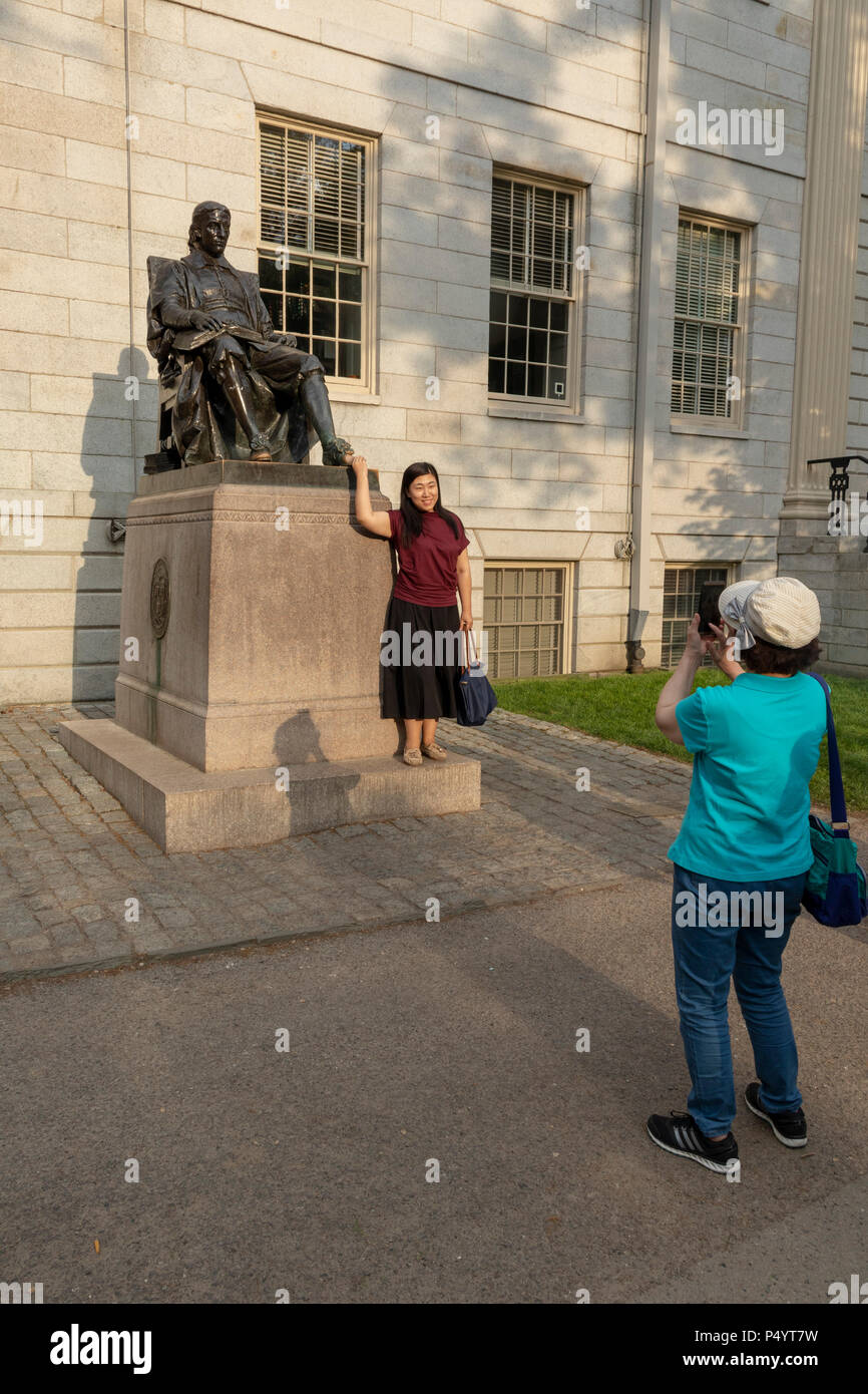 tourist being photographed rubbing toe of bronze statue of John Harvard by Daniel Chester French in Harvard Yard, Cambridge, Massachu­setts, USA - Stock Image