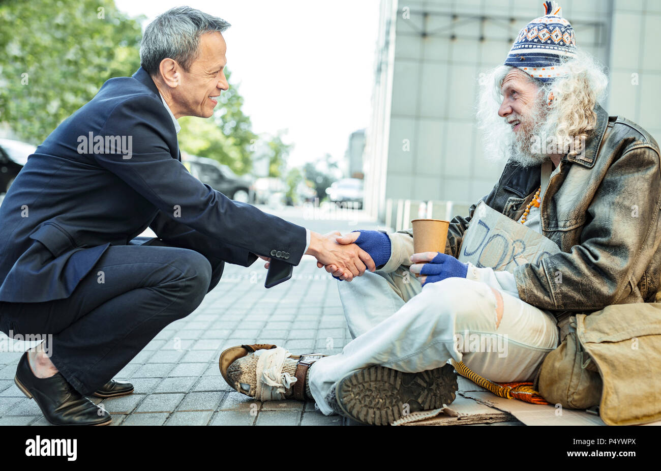 Smiling kind businessman shaking hand of starving man - Stock Image