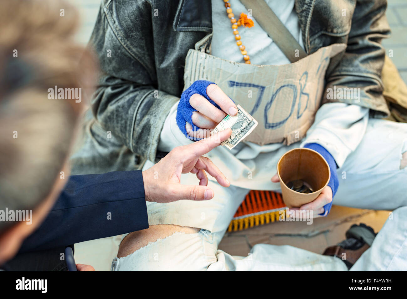 Homeless man wearing tattered trousers asking for money - Stock Image
