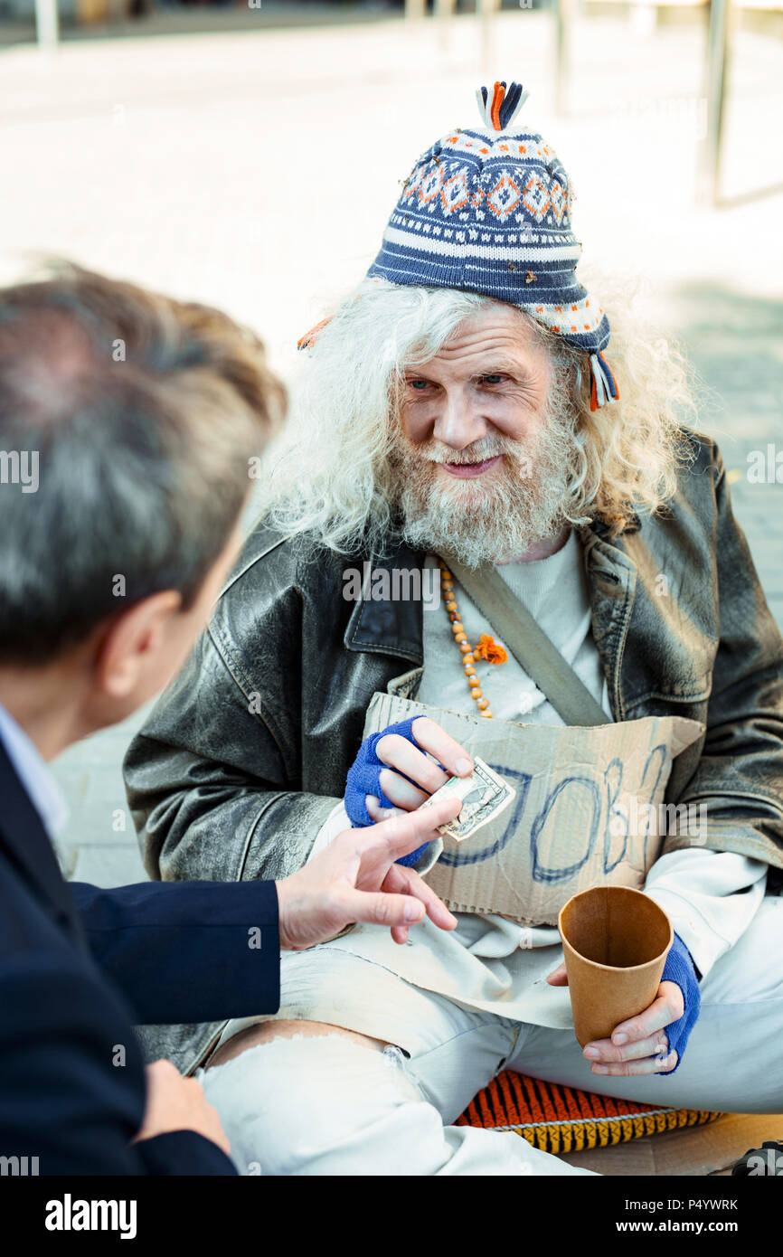 Unemployed elderly hippy man begging for help - Stock Image