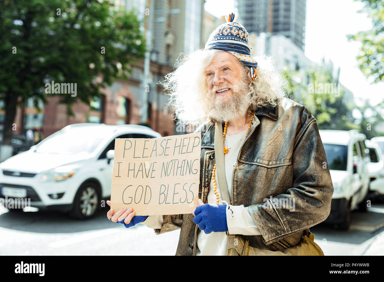 Starving fugitive asking for help standing in the street - Stock Image