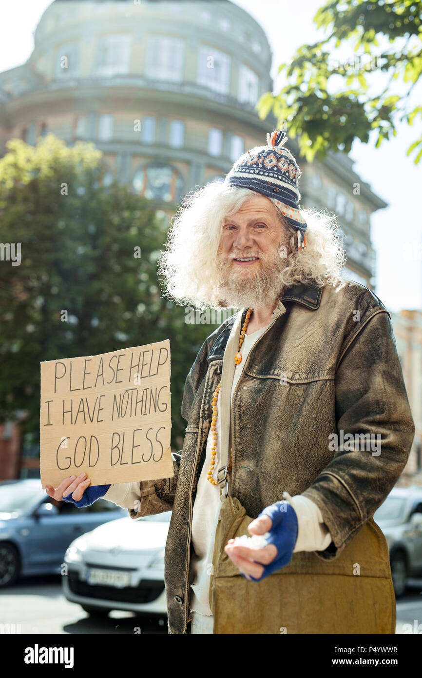 Homeless wearing old brown leather jacket - Stock Image
