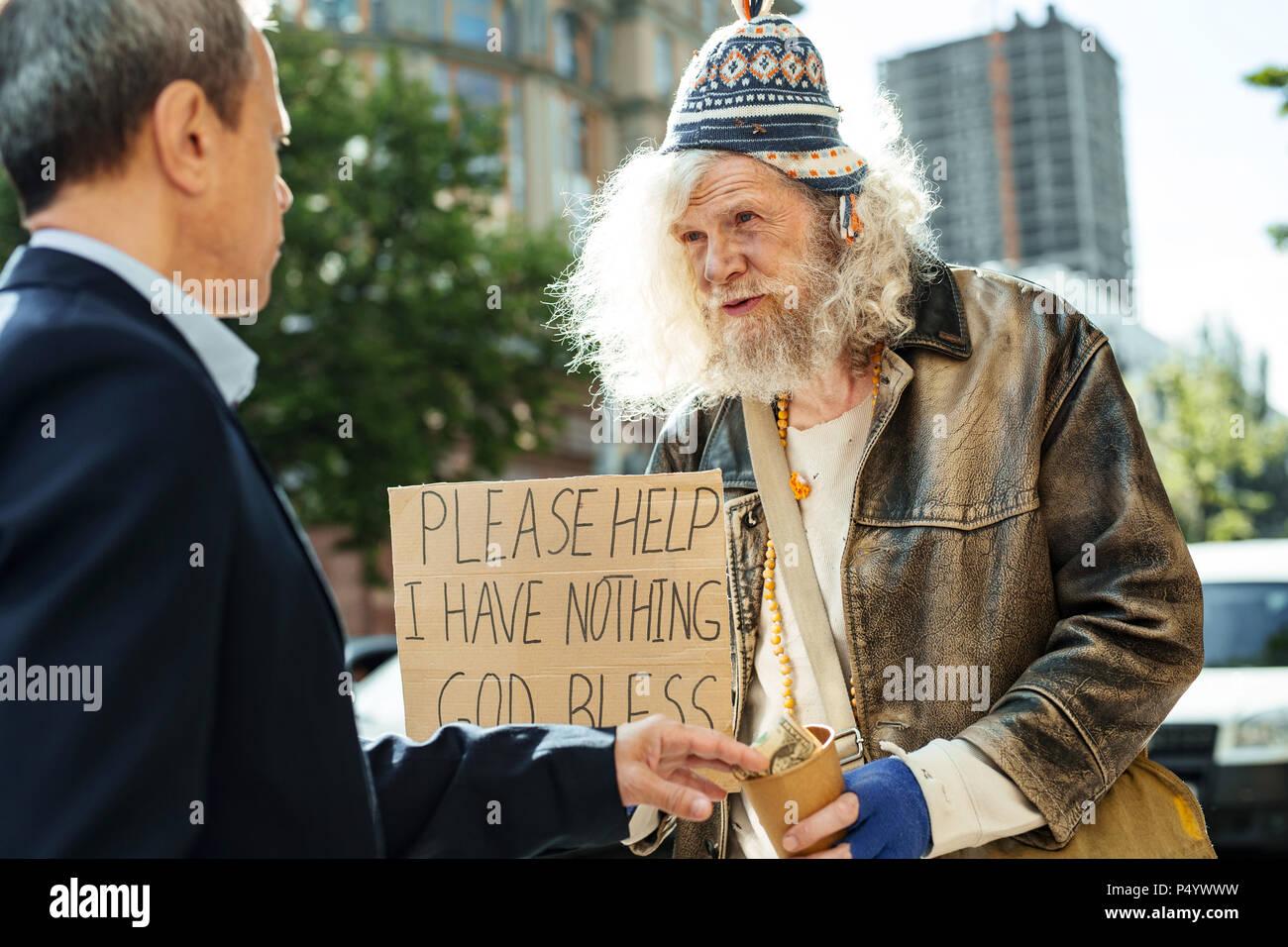 Prosperous office manager giving dollar bill to hopeless fugitive - Stock Image