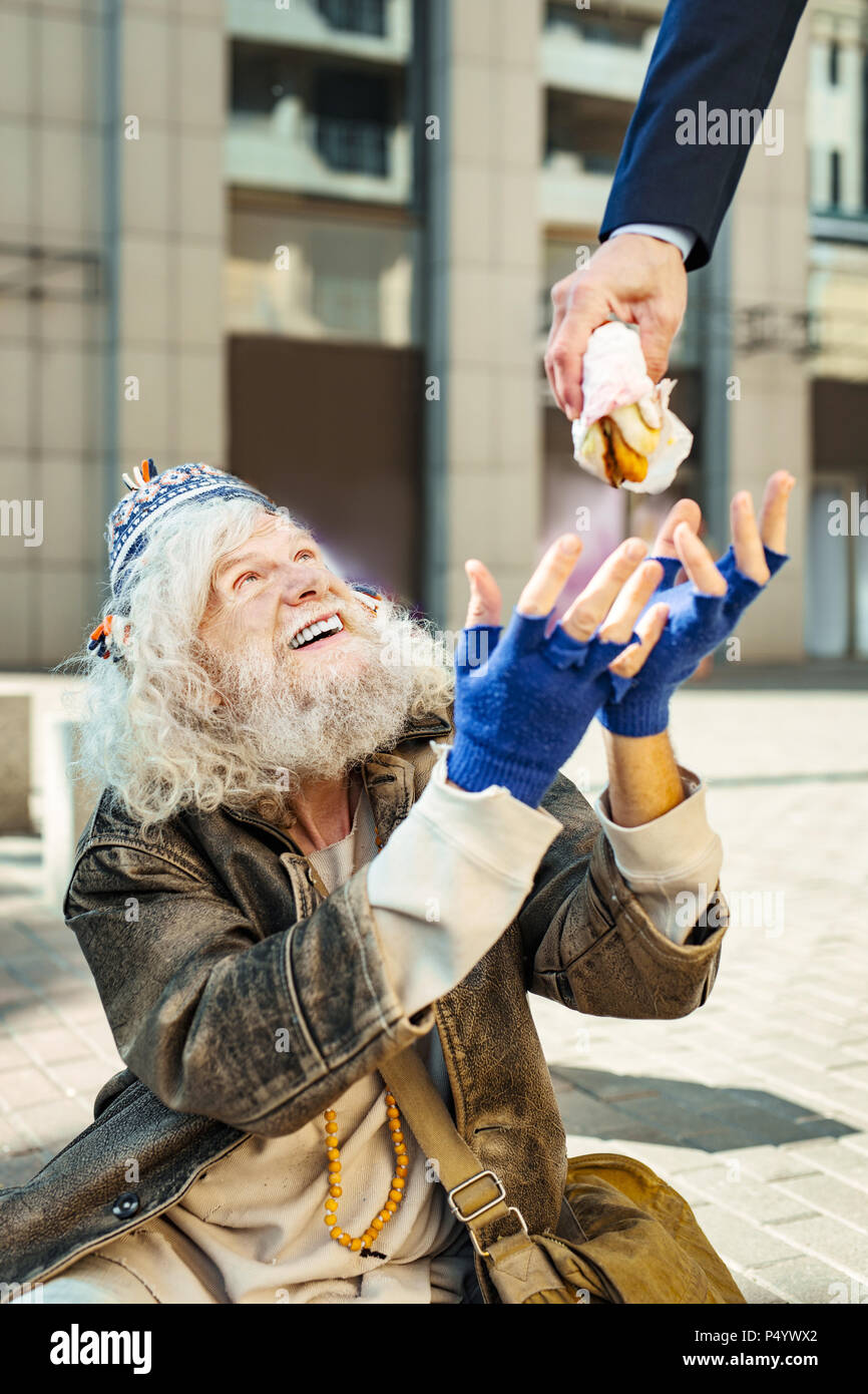 Homeless man feeling very happy looking at food - Stock Image