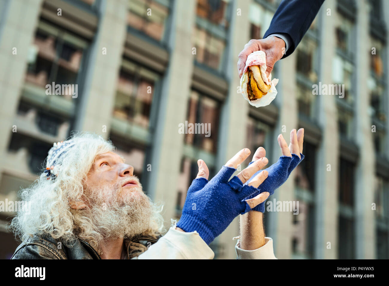 Street person begging for some food sitting near office center - Stock Image