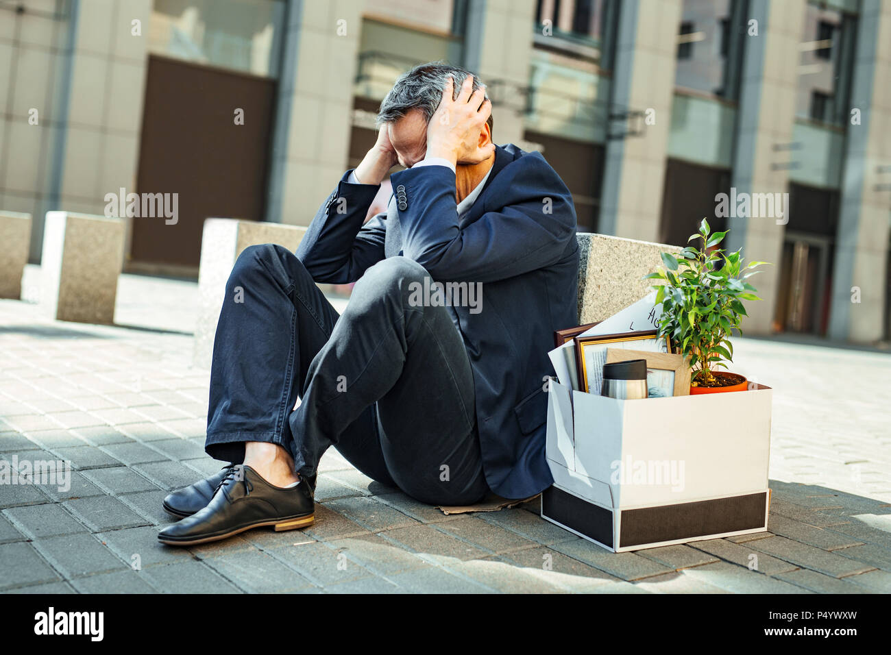 Elderly grey-haired man clutching his head while feeling panic - Stock Image