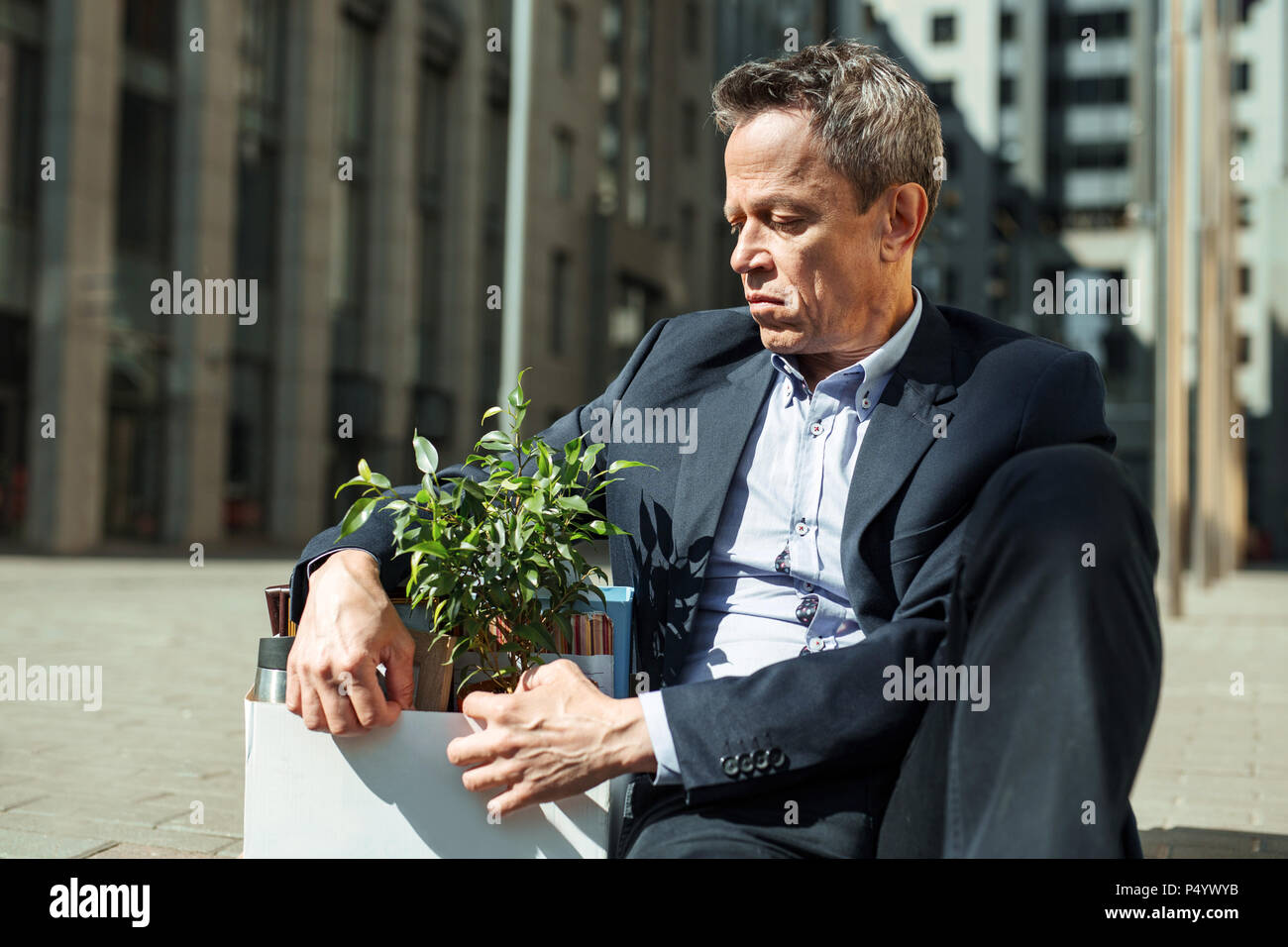 Grief stricken man feeling bad after being fired - Stock Image