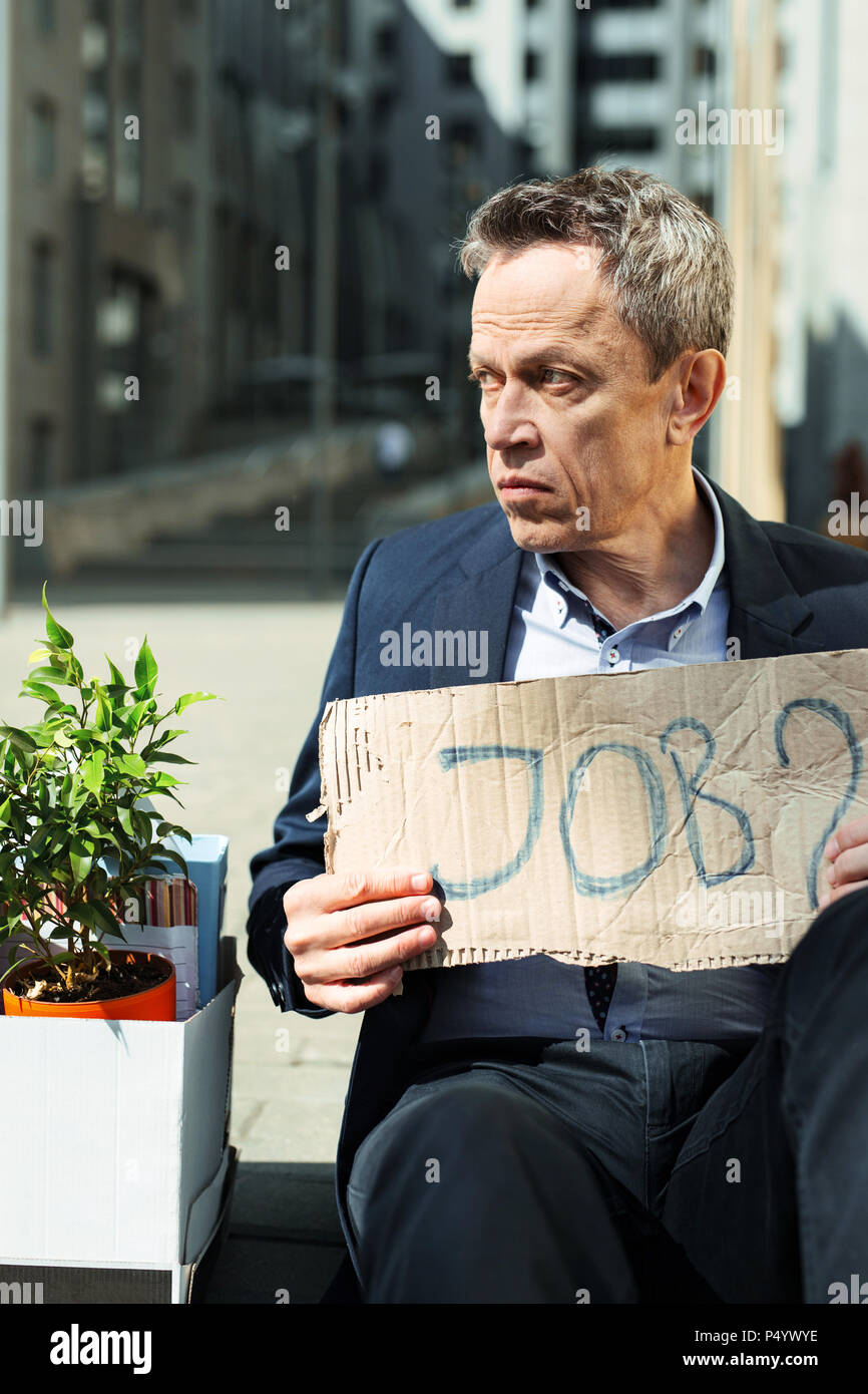 Brokenhearted fired man searching job outside - Stock Image