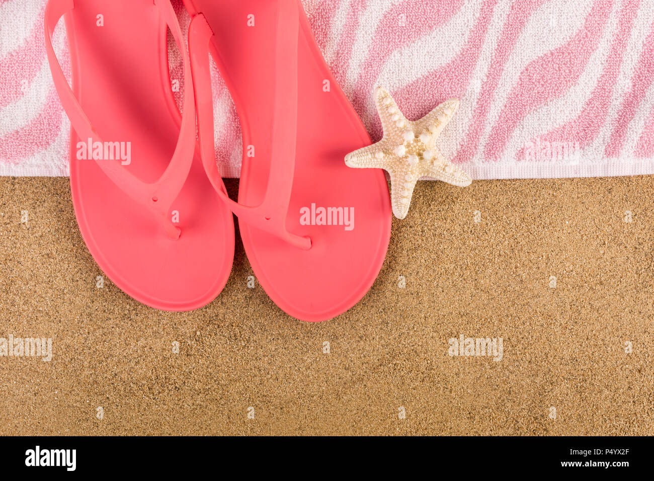 3f7923b63 Pink sandal flip flop and towel on sand beach and starfish. Summer  vacations copy space