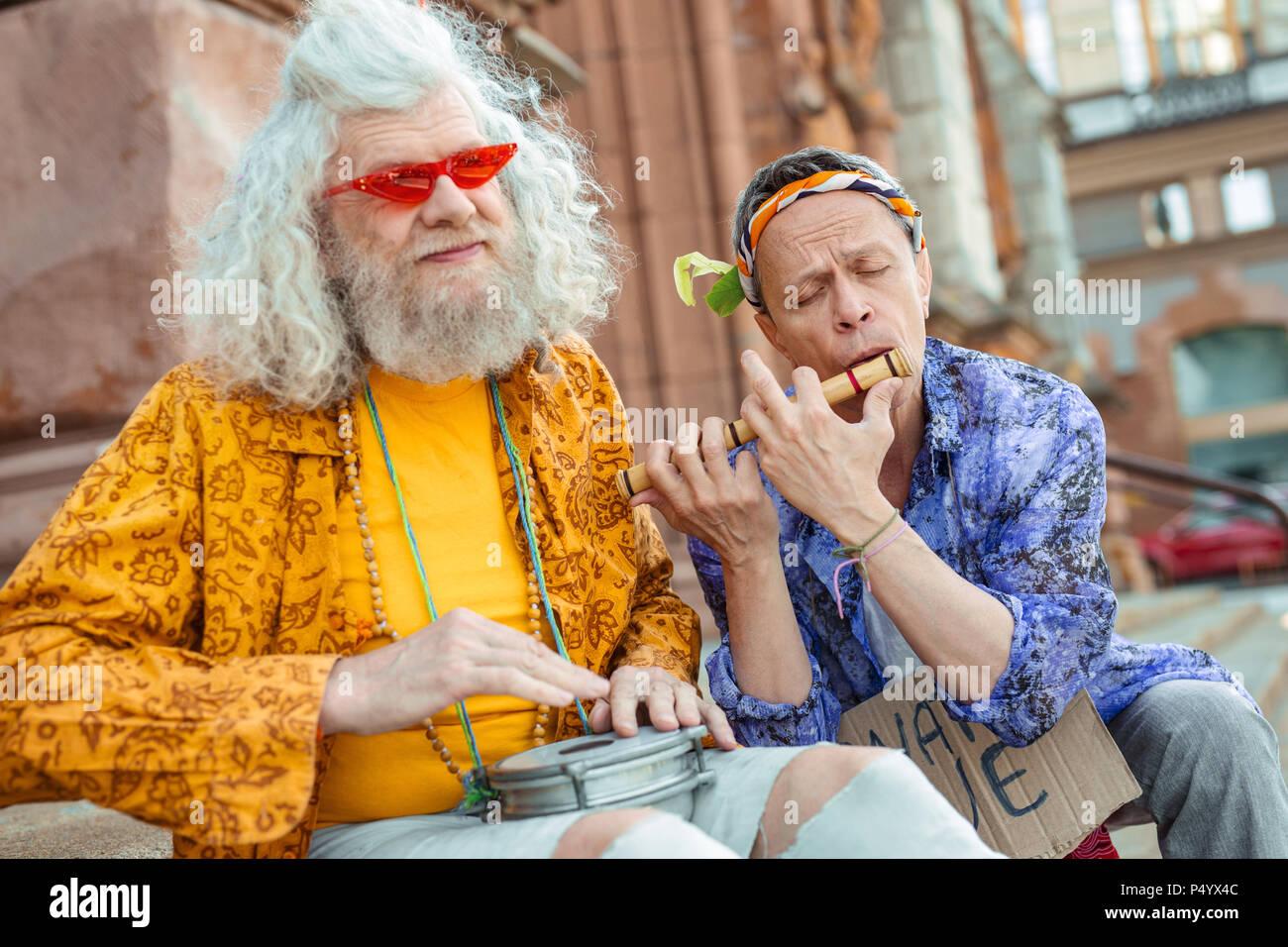 Two elderly flower-children enjoying their street performance - Stock Image