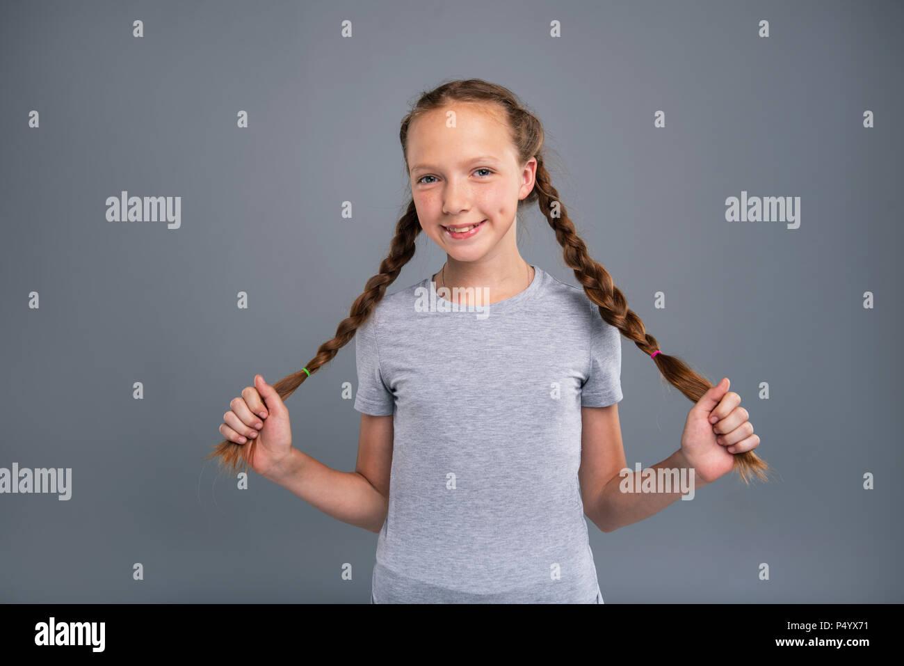 Cheerful teenage girl holding her two braids - Stock Image