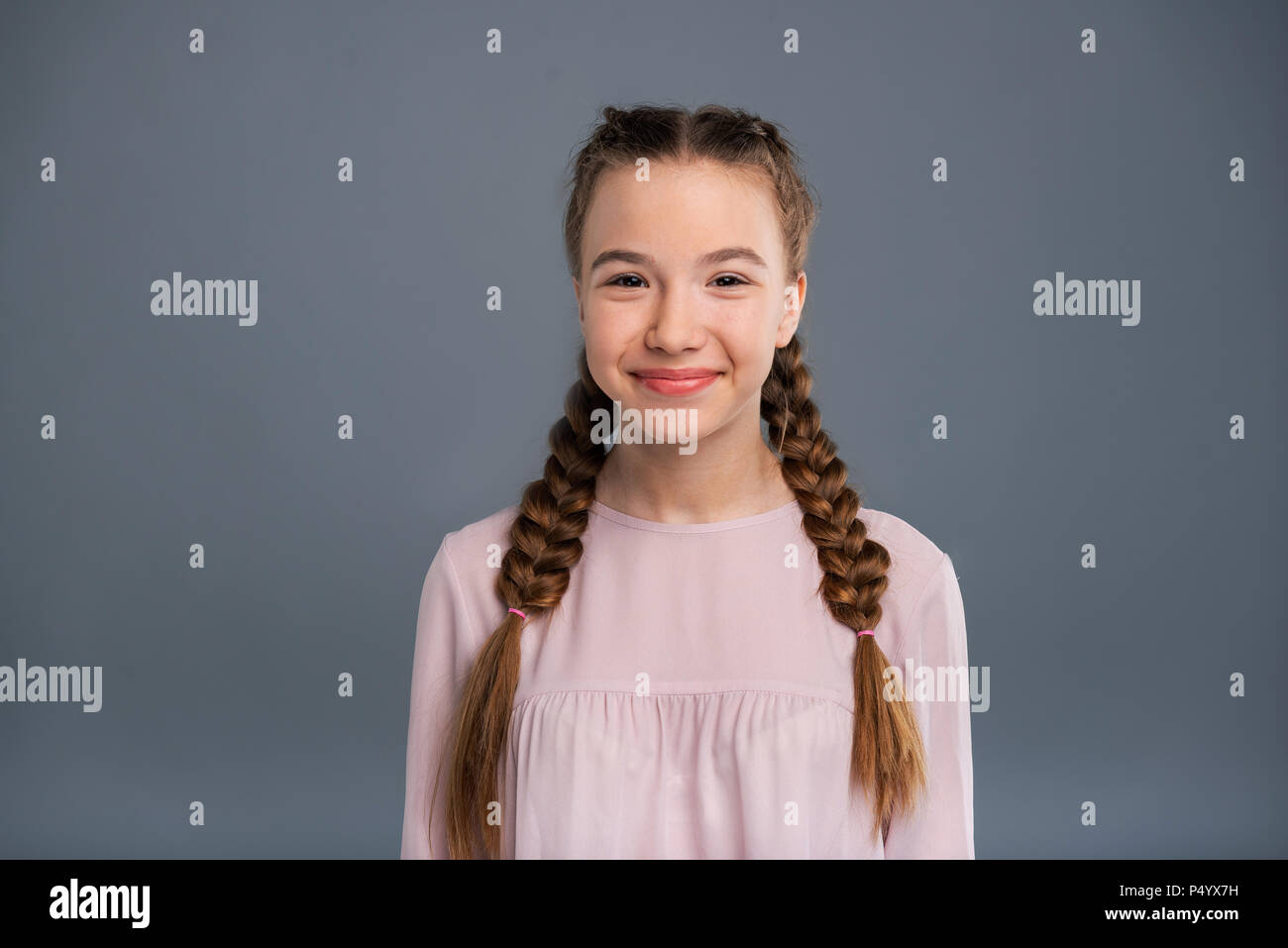 Portrait of a cute teenage girl with two braids - Stock Image