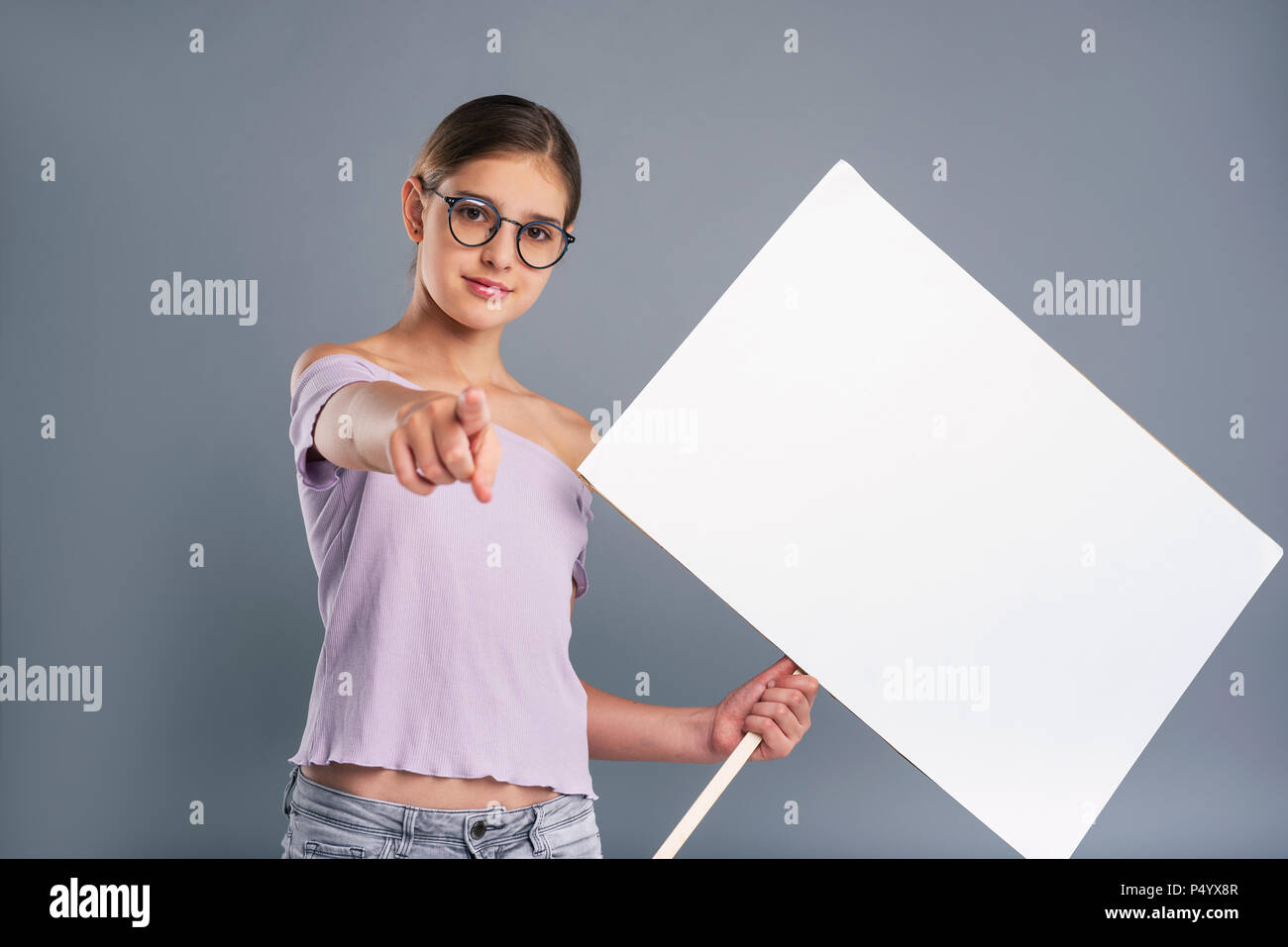 Cute teenage girl holding banner and pointing - Stock Image