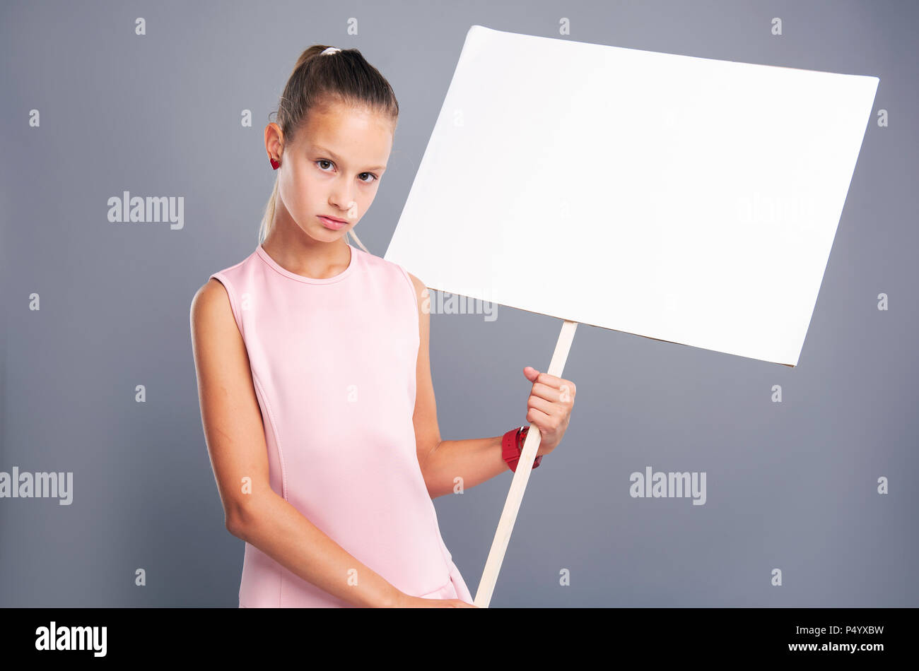Serious teenage girl holding empty banner - Stock Image