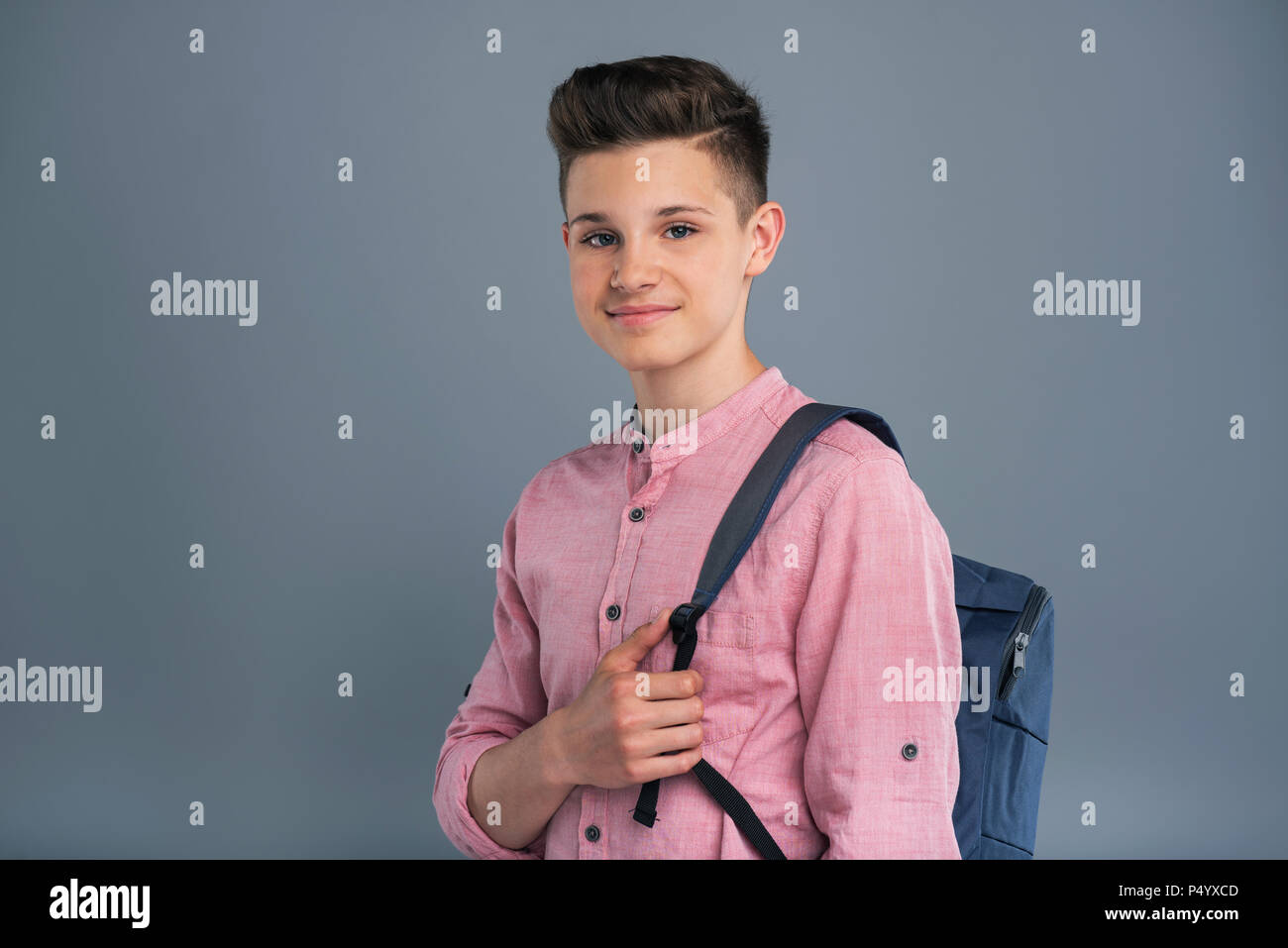 Pleasant teenage boy posing with a backpack - Stock Image