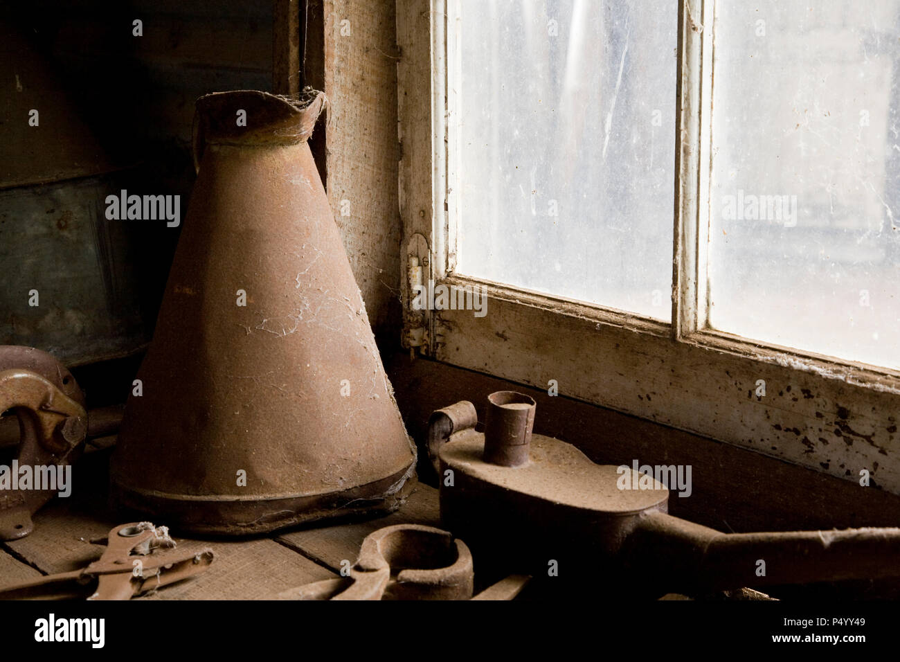 An old metallic ewer and antique tools in front of a workshop window. Stock Photo
