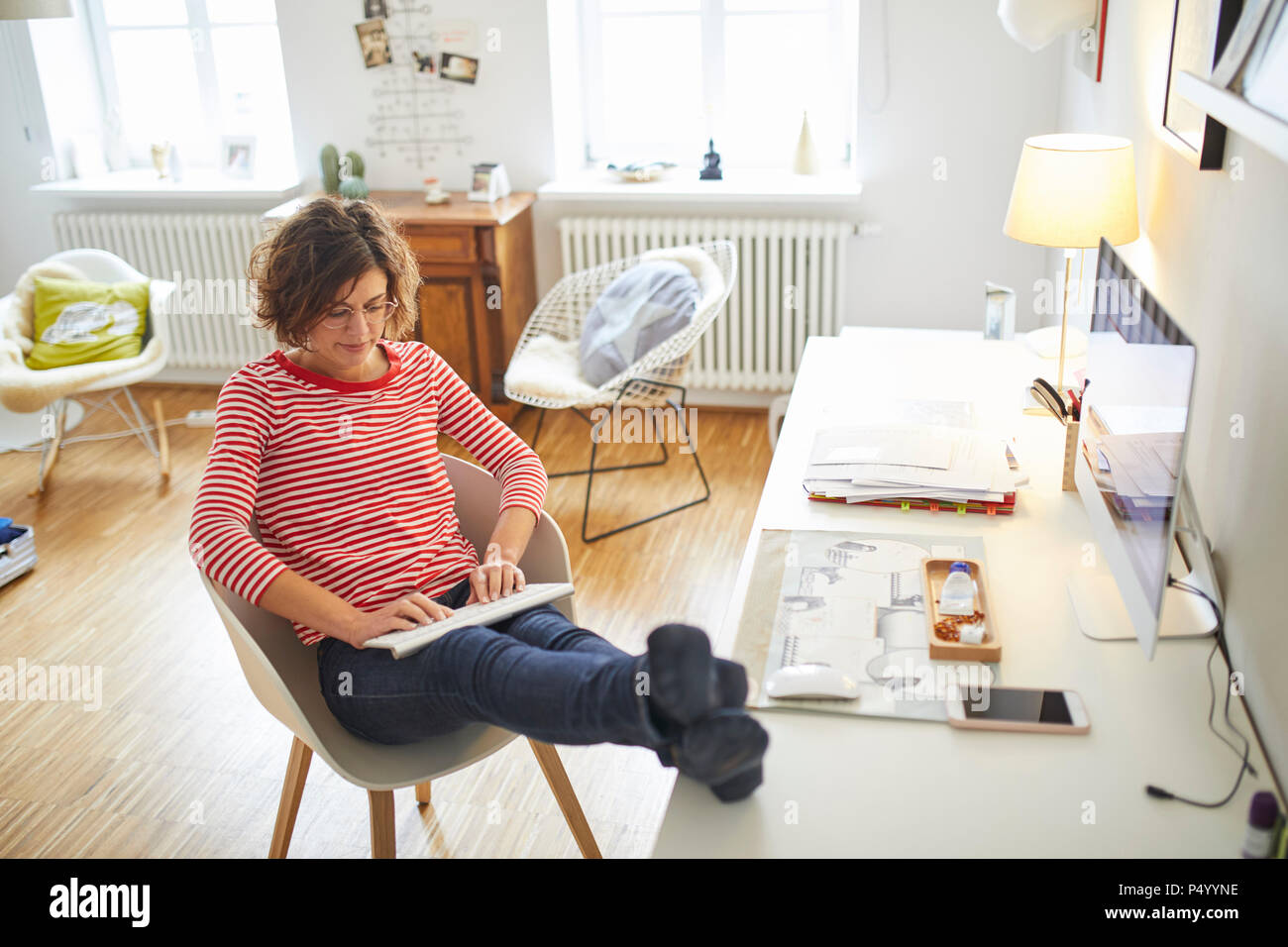 Mature woman sitting with feet up at desk at home using cordless keyboard - Stock Image
