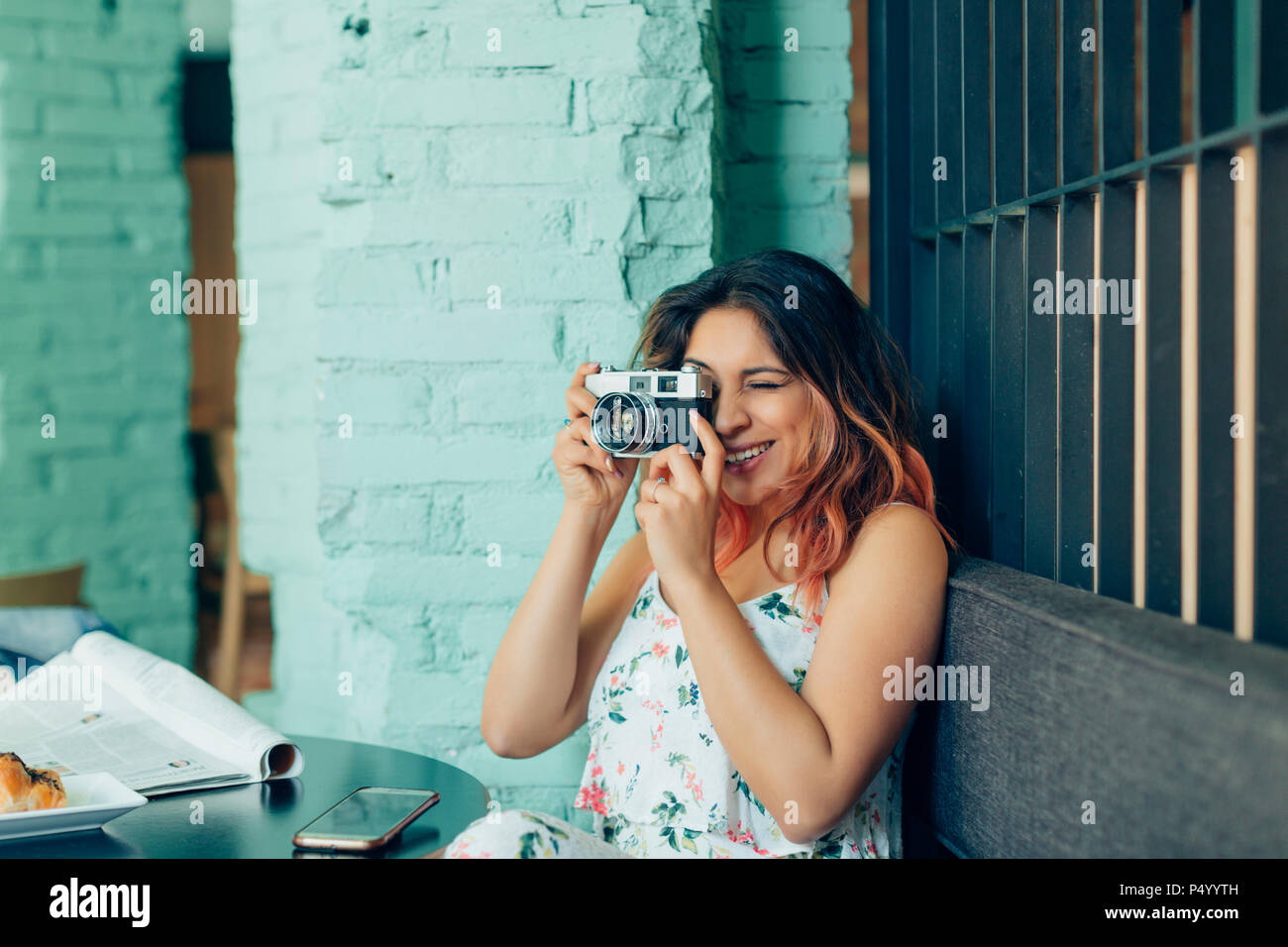 Smiling woman sitting in coffee shop taking pictures with camera - Stock Image