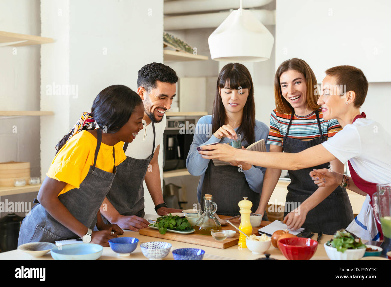 Happy friends and instructor in a cooking workshop - Stock Image