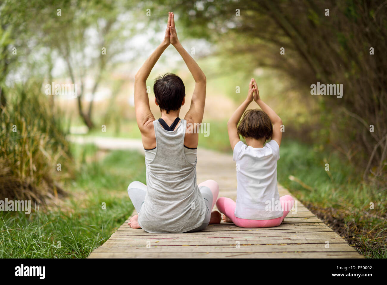 Rear view of mother and daughter doing yoga on boardwalk - Stock Image