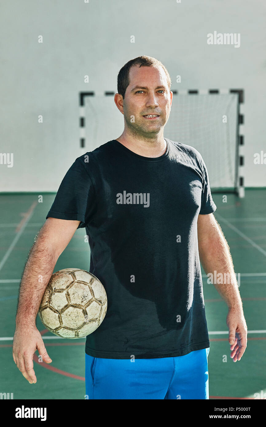 Portrait of indoor soccer player holding the ball - Stock Image