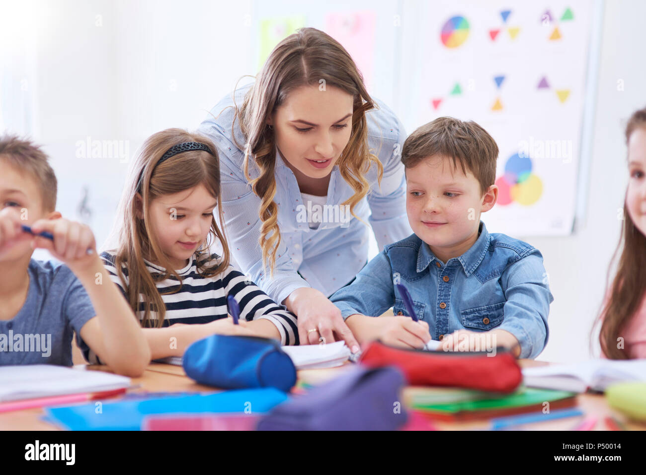 Teacher helping pupils with their tasks in class - Stock Image