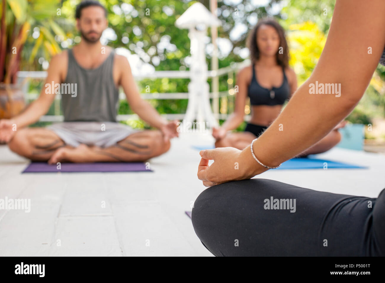 Two women and a man practicing yoga on terrace - Stock Image