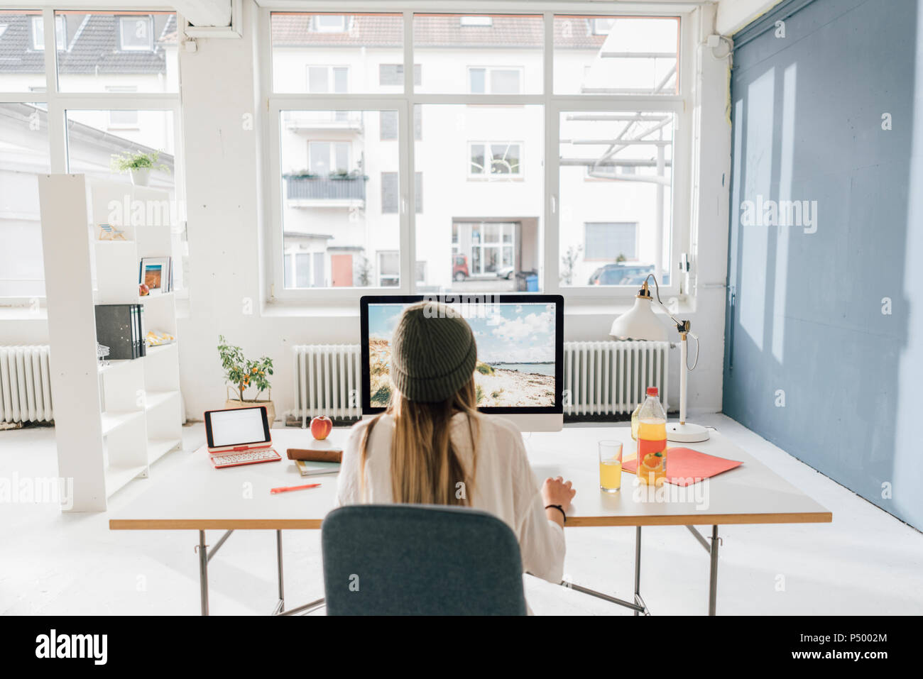 Back view of freelancer working at desk in a loft - Stock Image