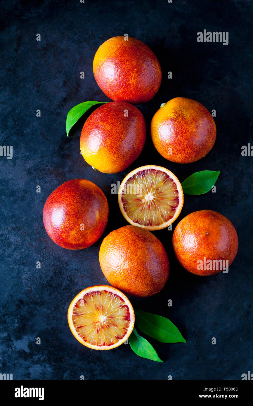 Whole and sliced blood oranges on dark ground Stock Photo
