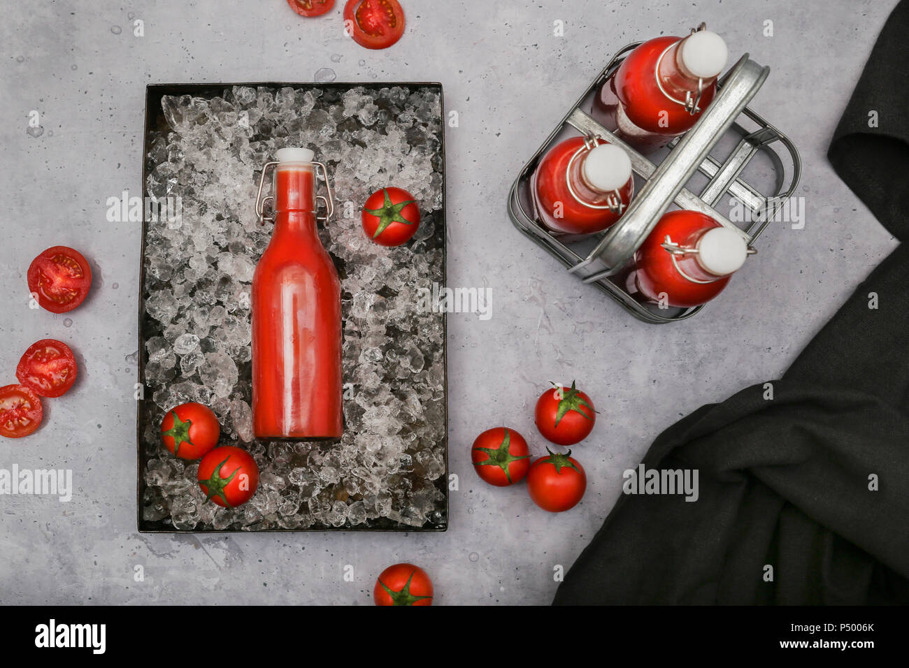 Ice-cooled homemade tomato juice in swing top bottle - Stock Image