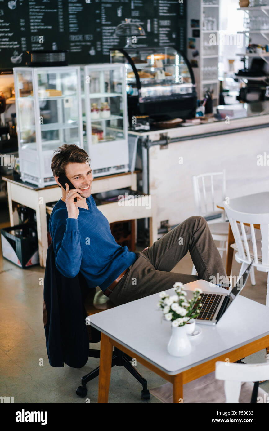 Smiling man in a cafe with laptop on cell phone Stock Photo